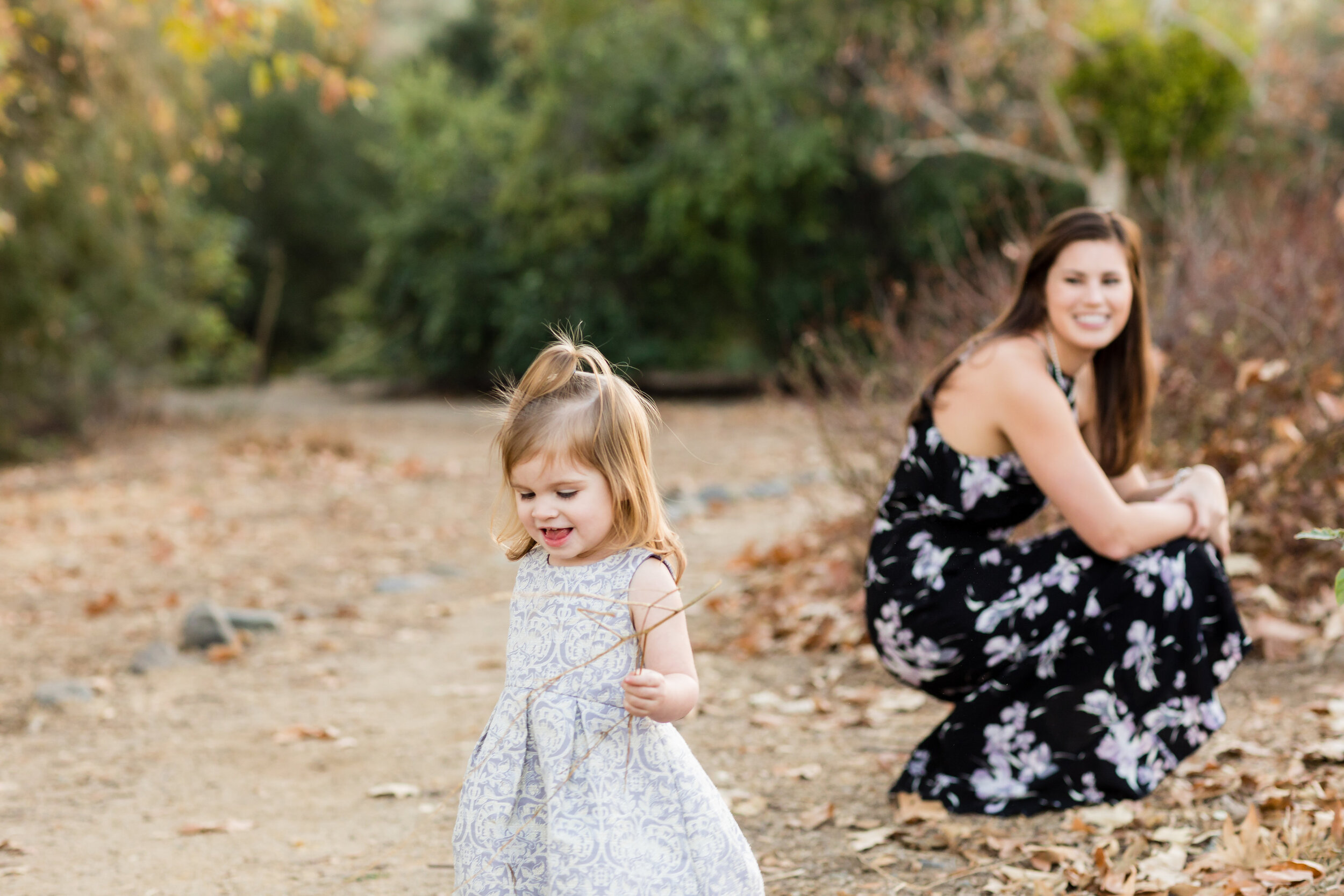 Daughter playing with leaves at Irvine Regional Park while Mother looks on.jpg