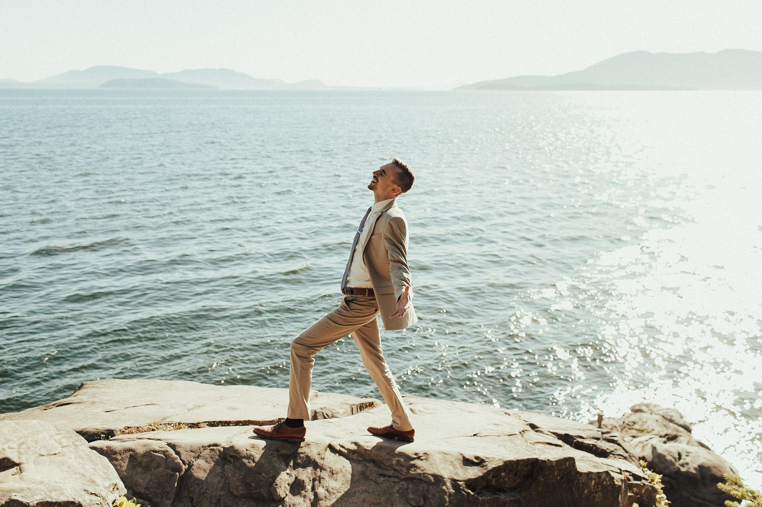 groom stands on the cliff at Larabee State Park in Bellingham WA