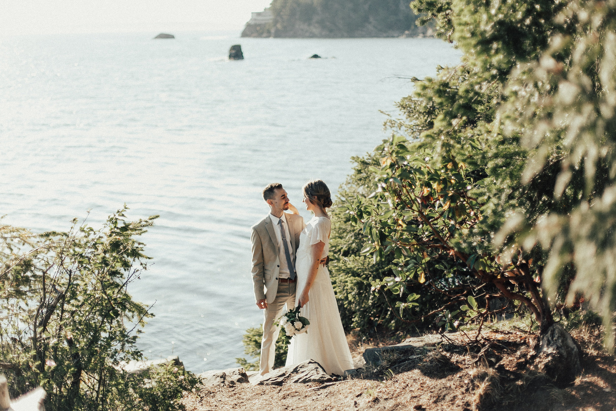 bride and groom stand on the cliffs in Bellingham WA