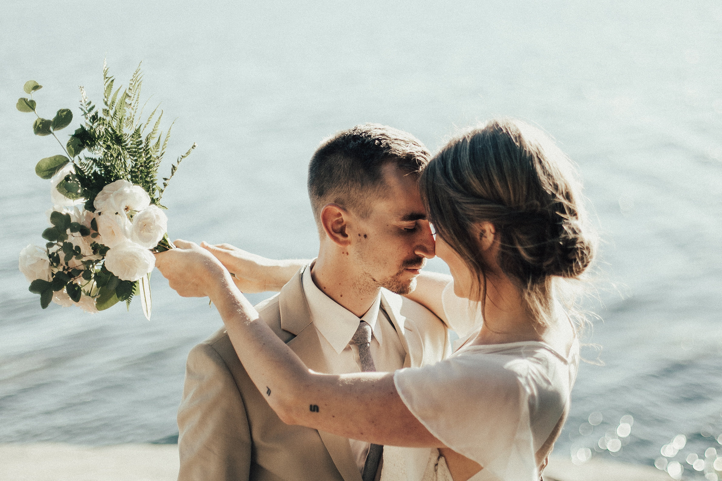 bride and groom cuddle near the water at Larabee State Park