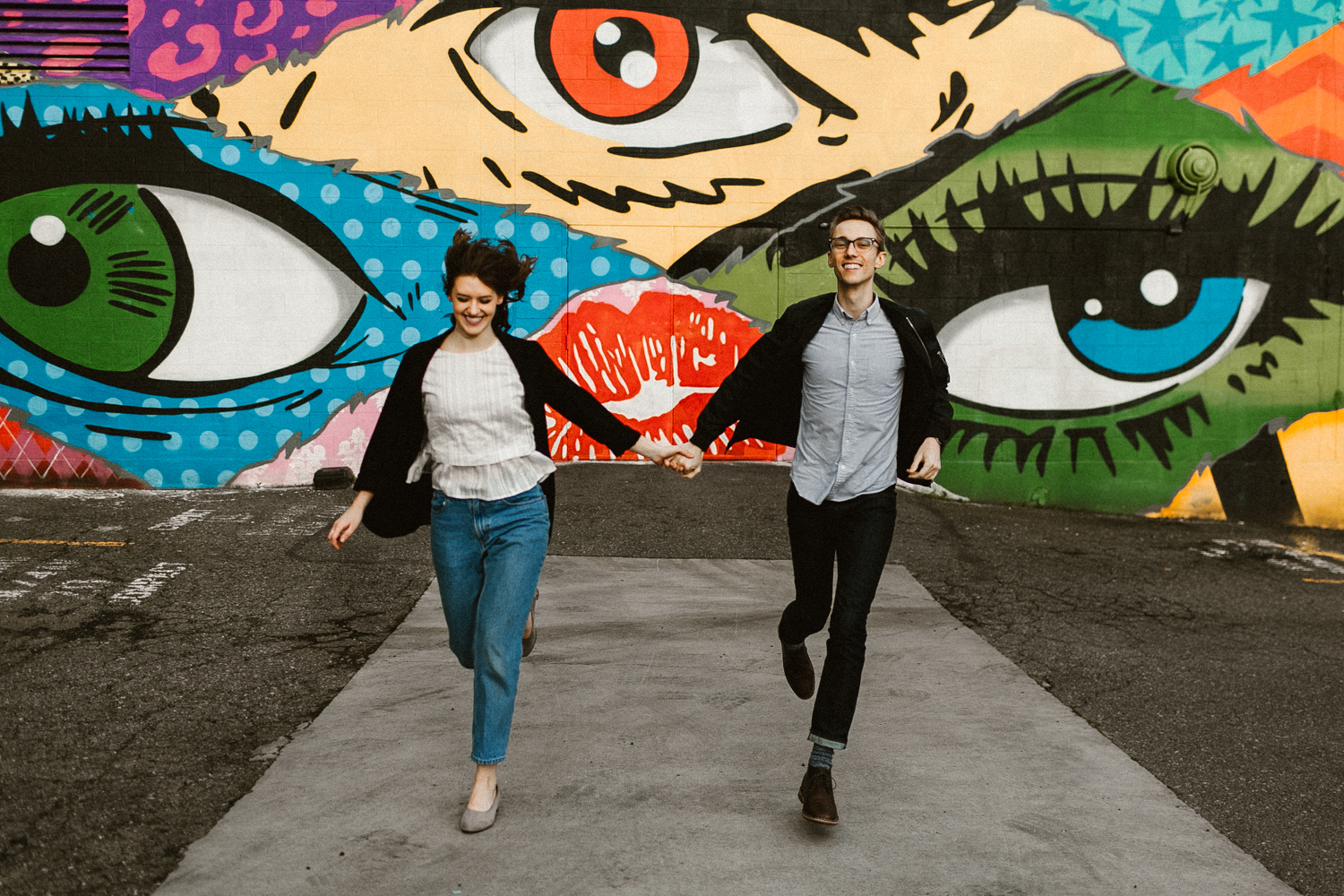 woman and man run in front of colorful mural in Seattle
