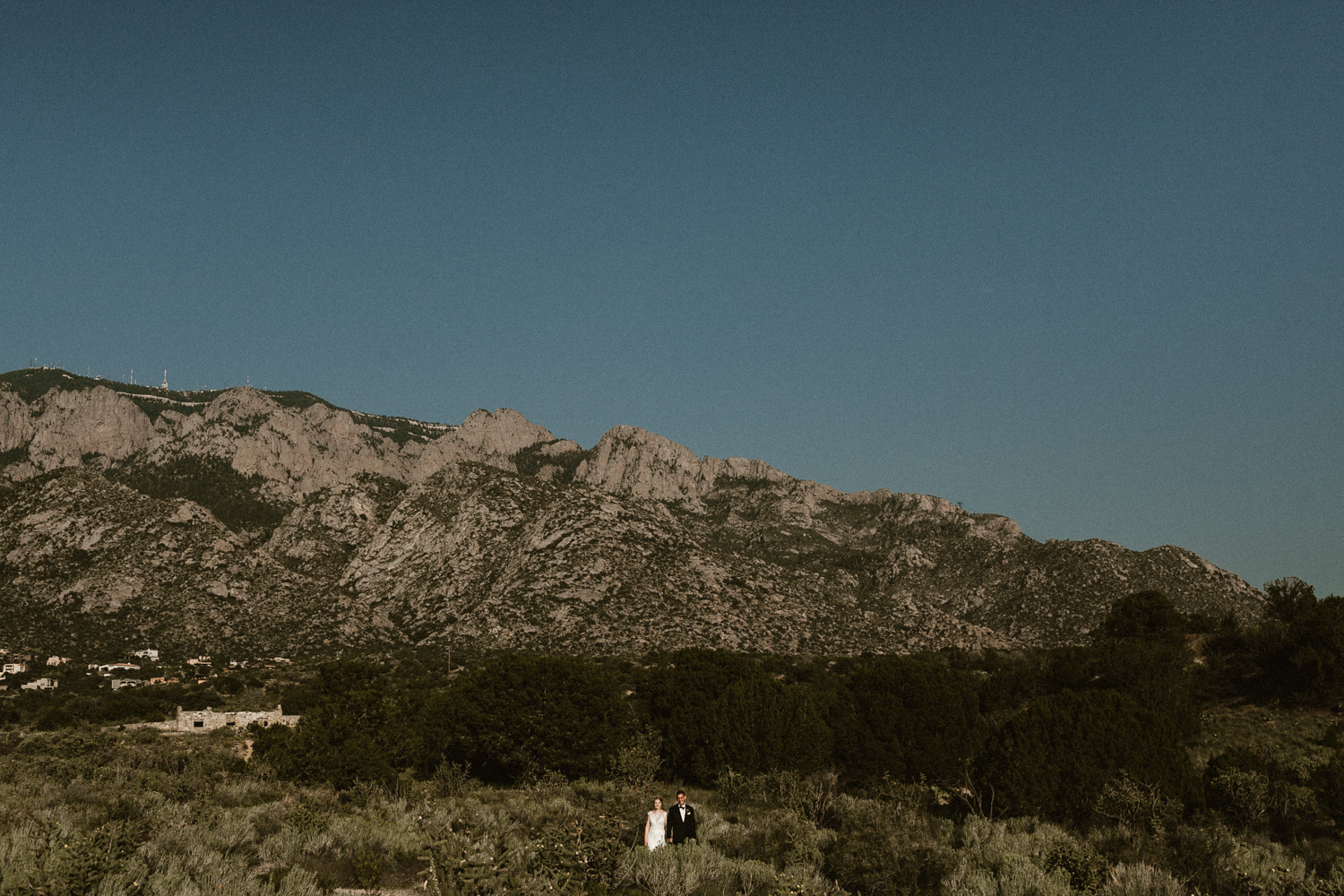 bride and groom stand beneath the Albuquerque Mountains