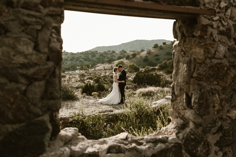 bride and groom cuddle in stone ruins in Albuquerque New Mexico
