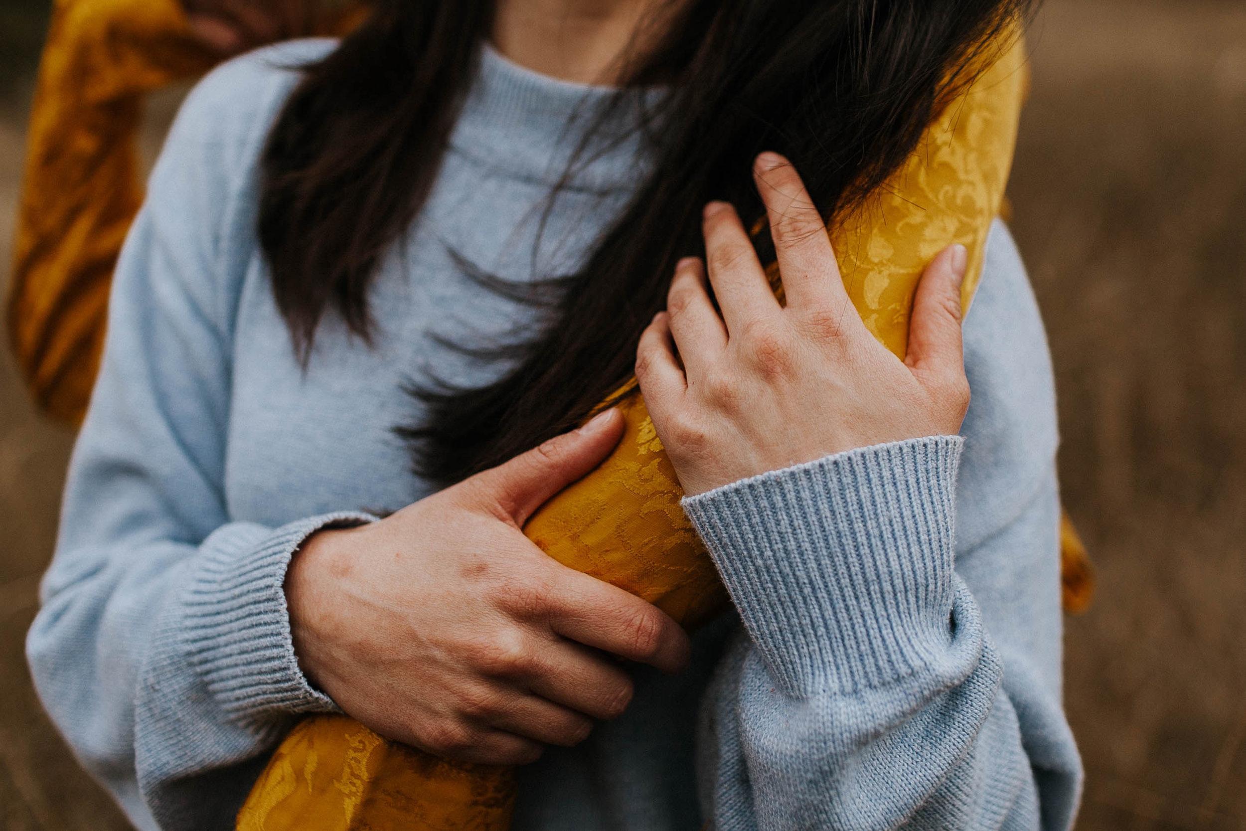 detail of a woman's hands in a grassy field in Seattle WA
