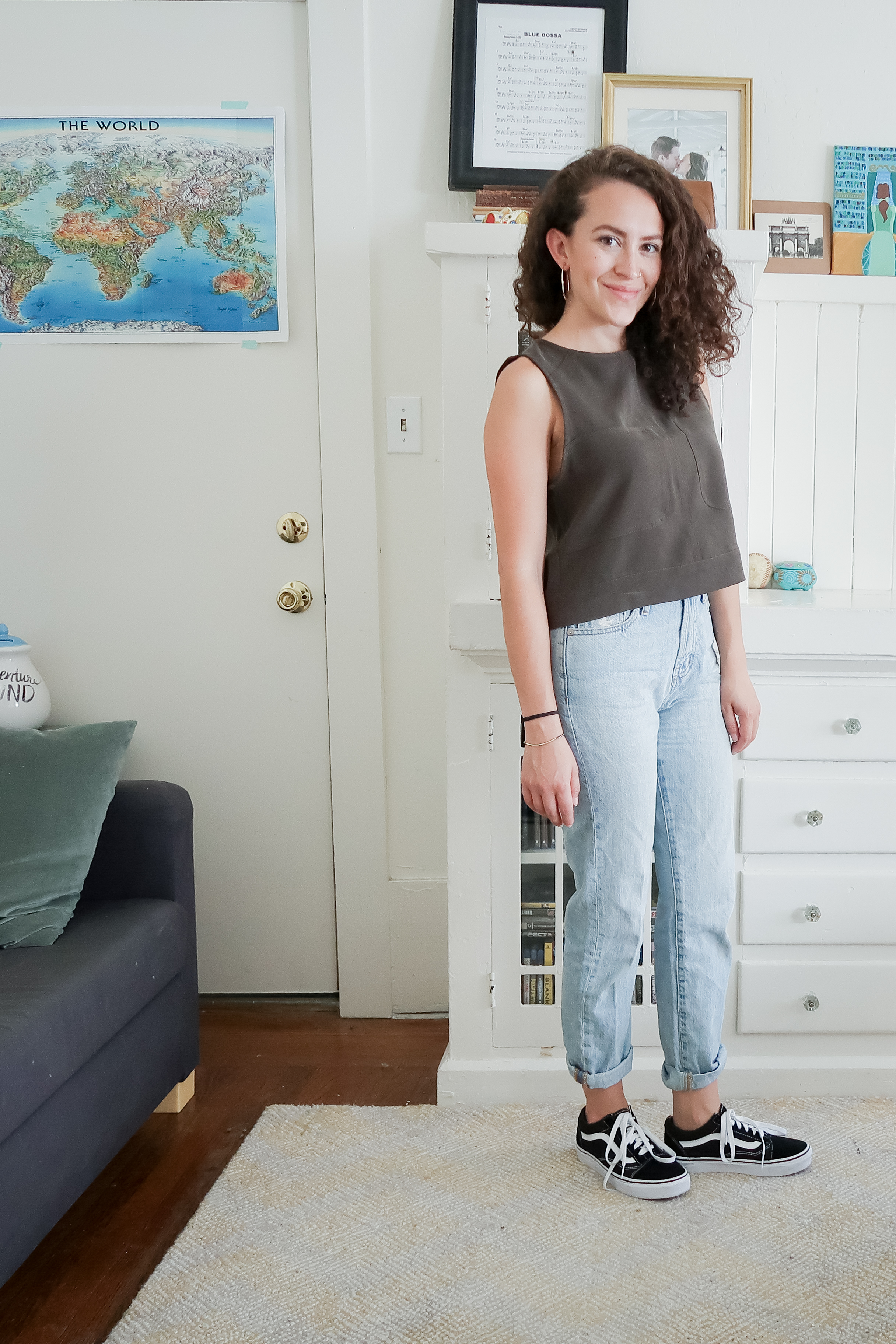 10 pieces, 10 outfits -- an olive green boxy crop top worn with light wash high rise mom jeans (aka the perfect summer jean from madewell) and low top old skool vans sneakers