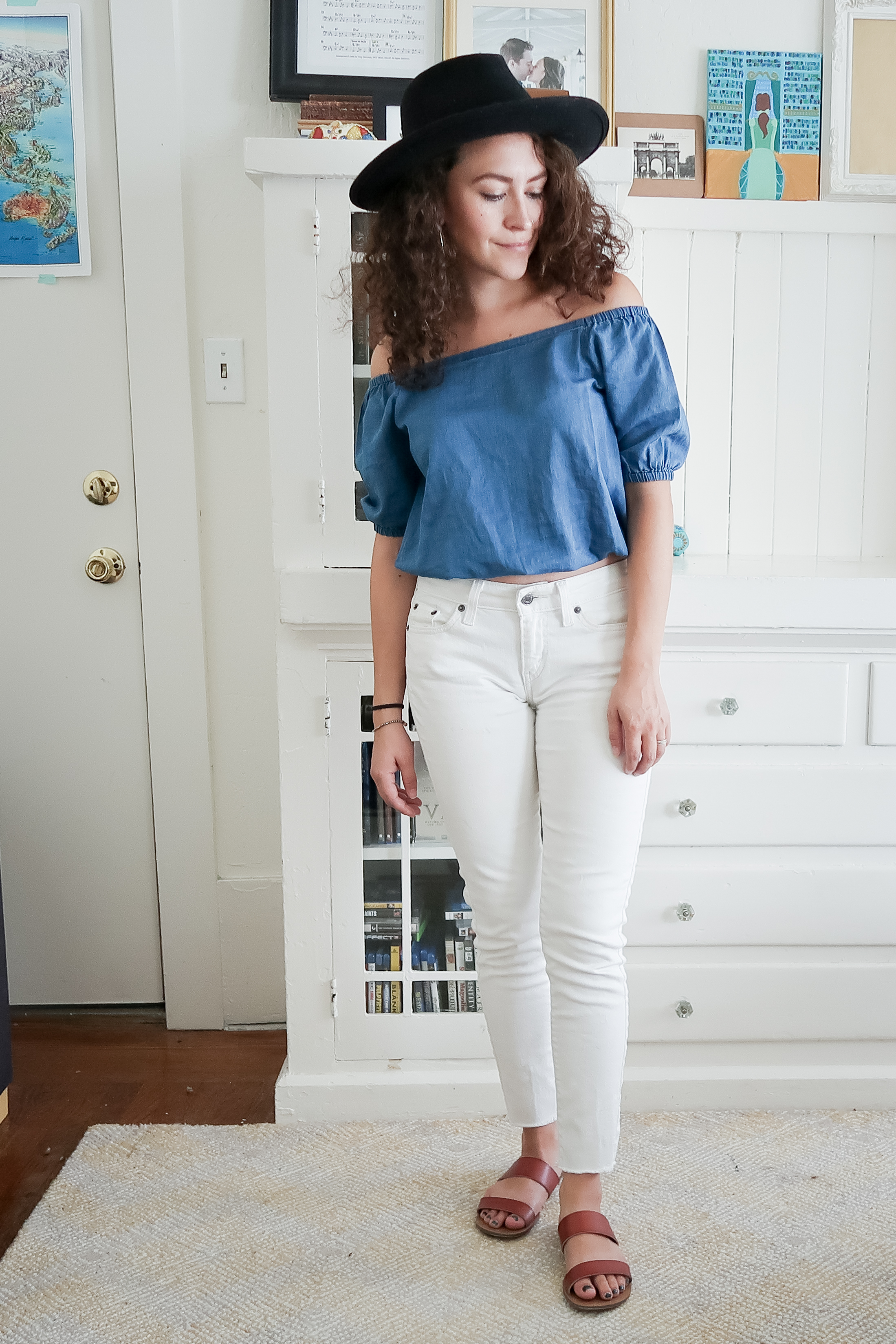 10 pieces, 10 outfits -- white levis skinny jeans worn with a bright indigo off the shoulder top from madewell, brown leather slide sandals and a black hat