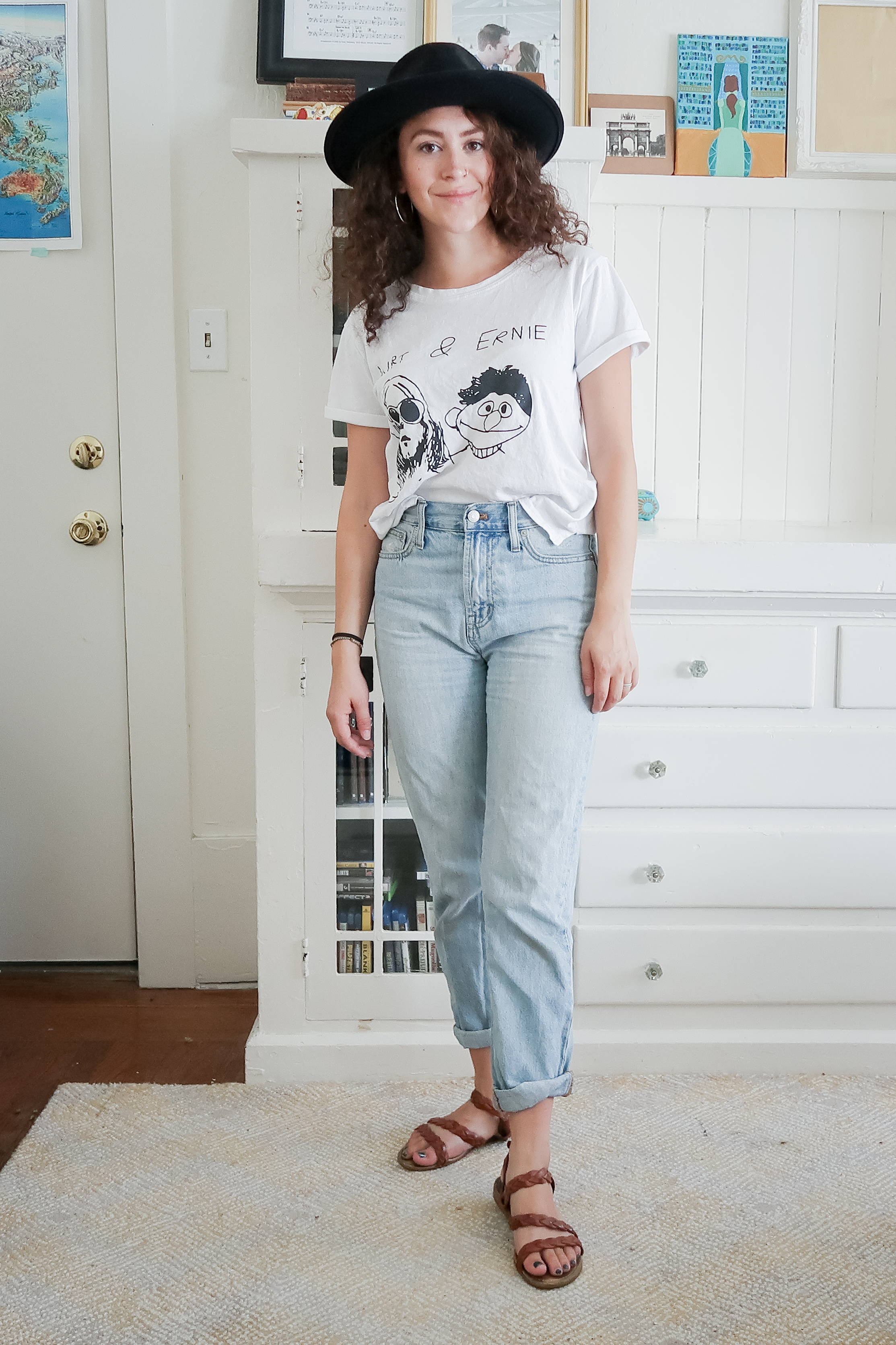 10 pieces, 10 outfits -- high rise light wash mom jeans (aka the perfect summer jean from madewell) styled with a white graphic tee, braided leather sandals and a black fedora