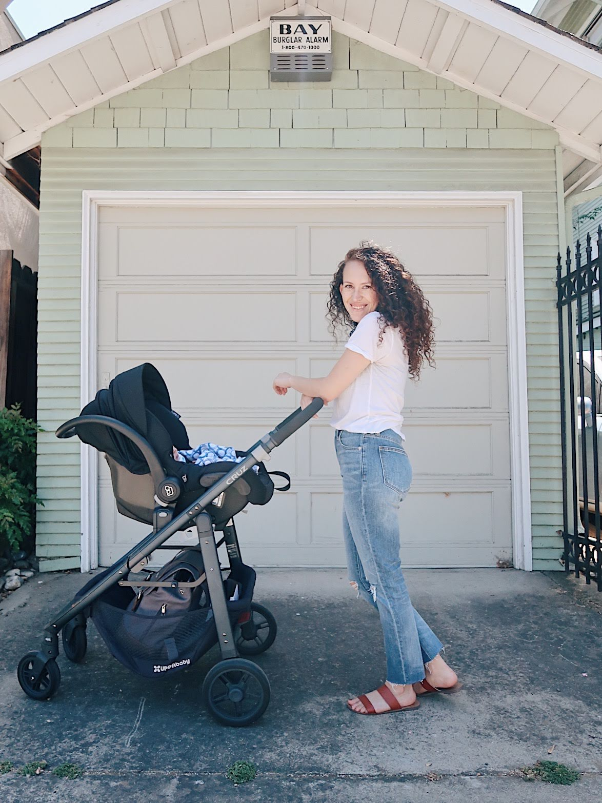 casual but chic way to wear boyfriend jeans. white v neck tee, madewell high rise slim boyjeans, slide sandals by j crew. bandana outfit. nursing friendly outfit. weekend outfit. uppababy cruz stroller