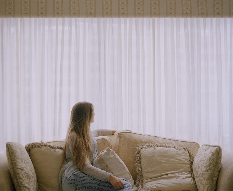 15. Girl sat in her living room.jpg