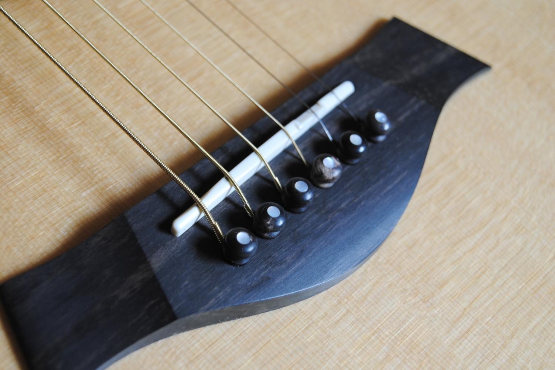 Der Steg einer Western-Gitarre: die Saiten werden hier mithilfe von  Bridge-Pins  befestigt.