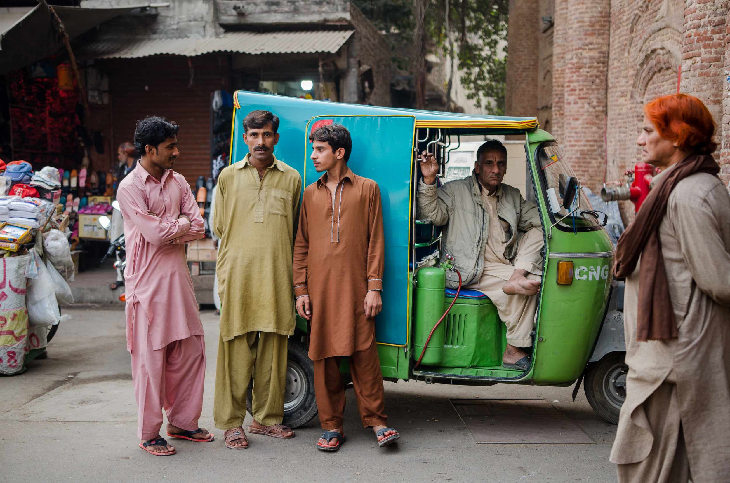 Men pose in front of an auto rickshaw in Lahore.