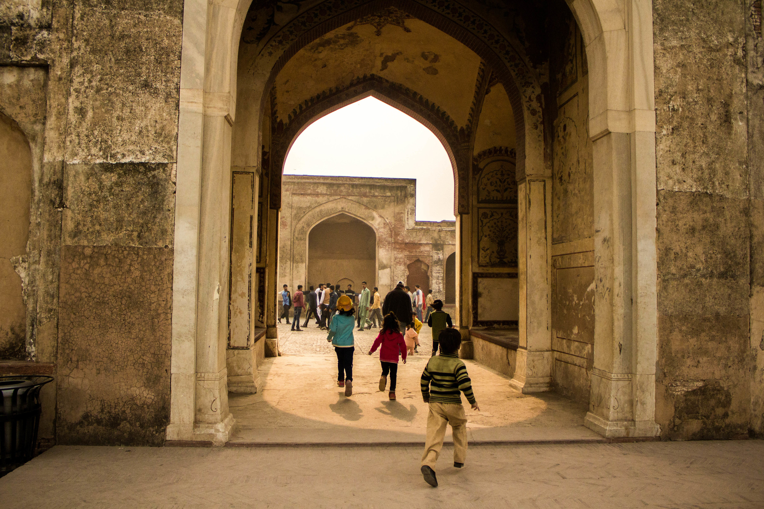 Children race through an archway into a courtyard in Lahore Fort
