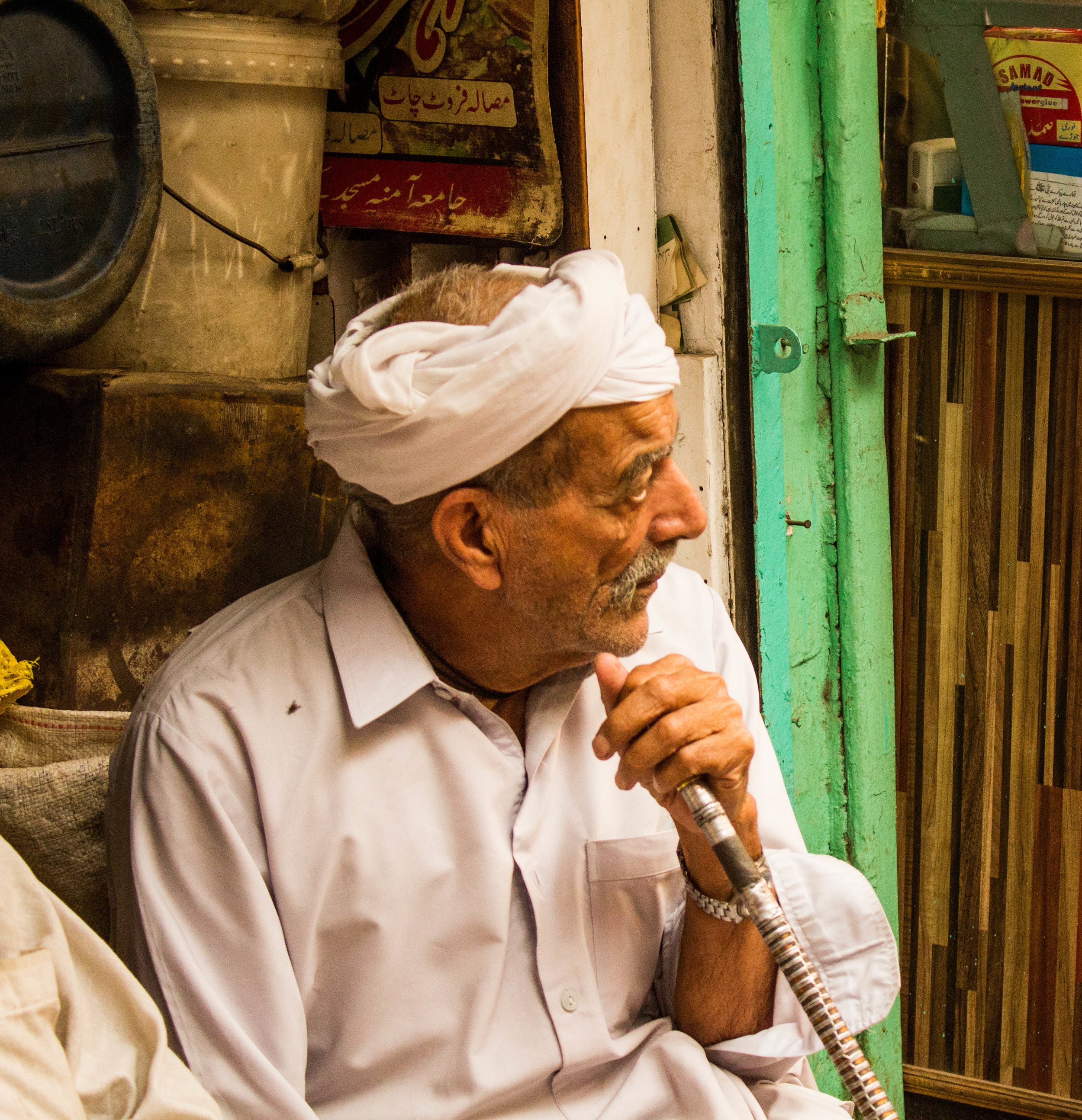 An elderly man people watches near the Lahori gate of Old Lahore.