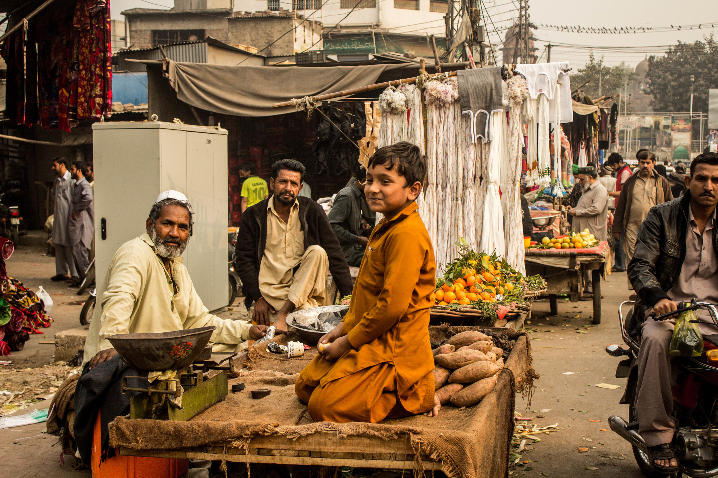 Three generations of vegetable sellers pause with their cart outside of Delhi gate.