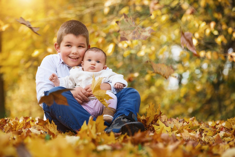 Podzimní portrét sourozenců v zabarveném listí ve Smetanových sadech v Olomouci. Starší bratr drží holčičku v náručí a oba sledují padající listí.