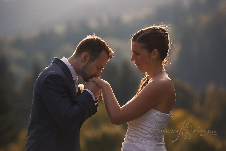 Svatební portrét ženicha a nevěsty na louce u horského hotelu Čarták v Beskydech.