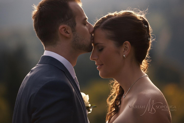 Intimní svatební portrét. Ženich dává polibek nevěstě na čelo.