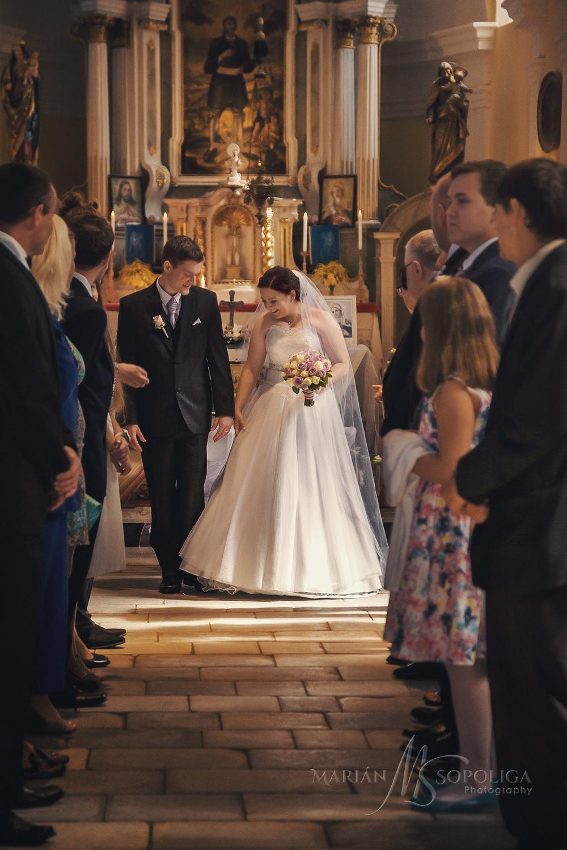 Nevěsta se ženichem odchází špalířem v kostele Sv. Isidora v Nových Losinách.