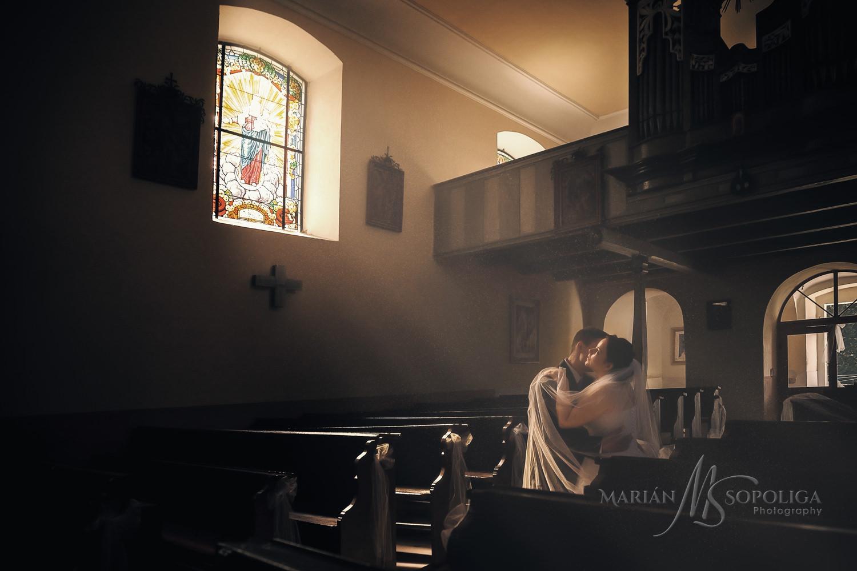 Romantický umělecký portrét ženicha a nevěsty v milostném objětí. Louče světla dopadají na zailovaný pár z okna v kostele.
