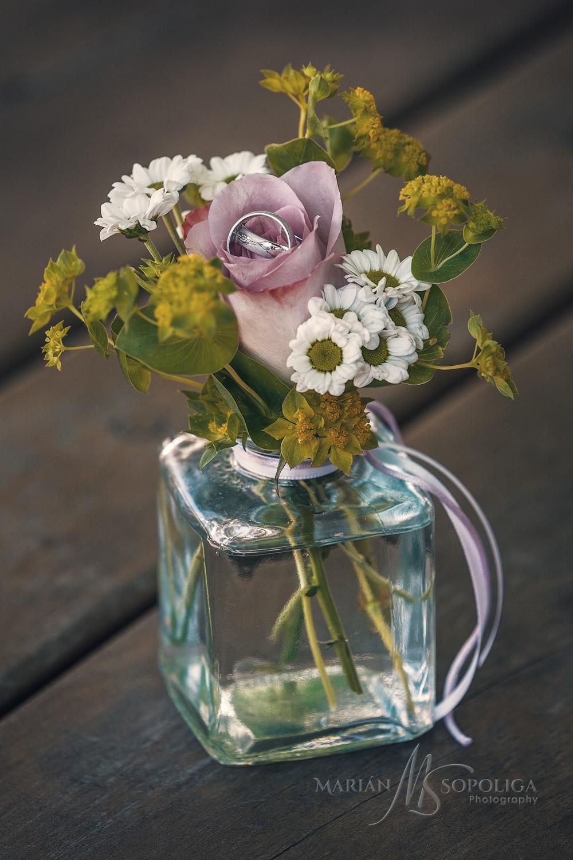 Detail svatebních prstýnků. Aranžovaná fotografie kytice ve skle s prstýnky.