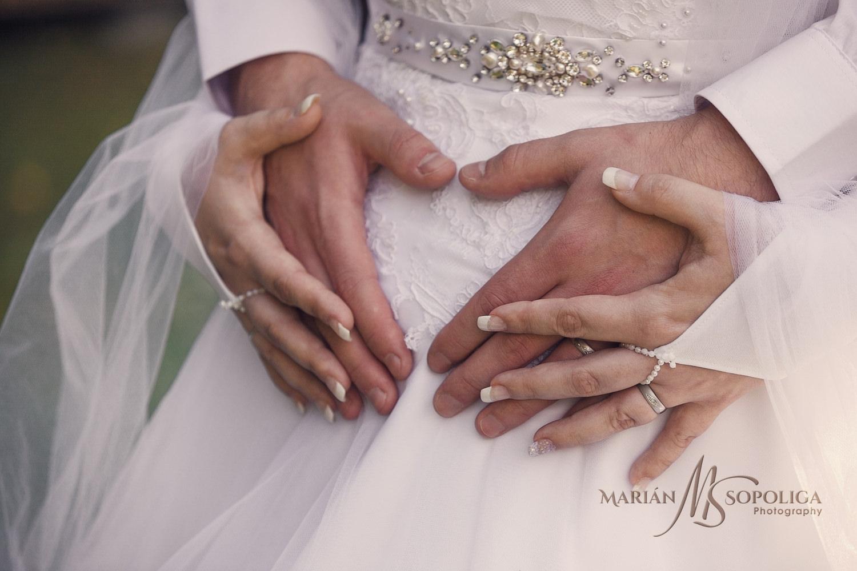 Detailní záběr na ruce ženicha a nevěsty vytvářející srdíčko.