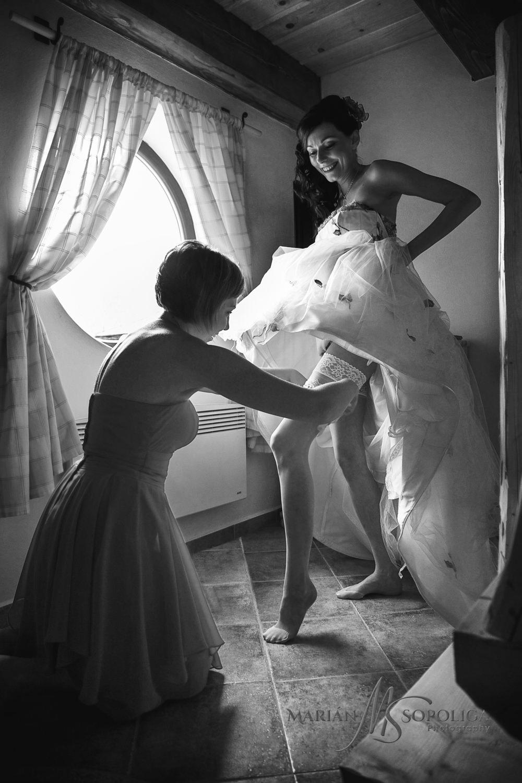 Družička navlíká podvazek nevěstě na svatbě v Podlesí, Vysočina.