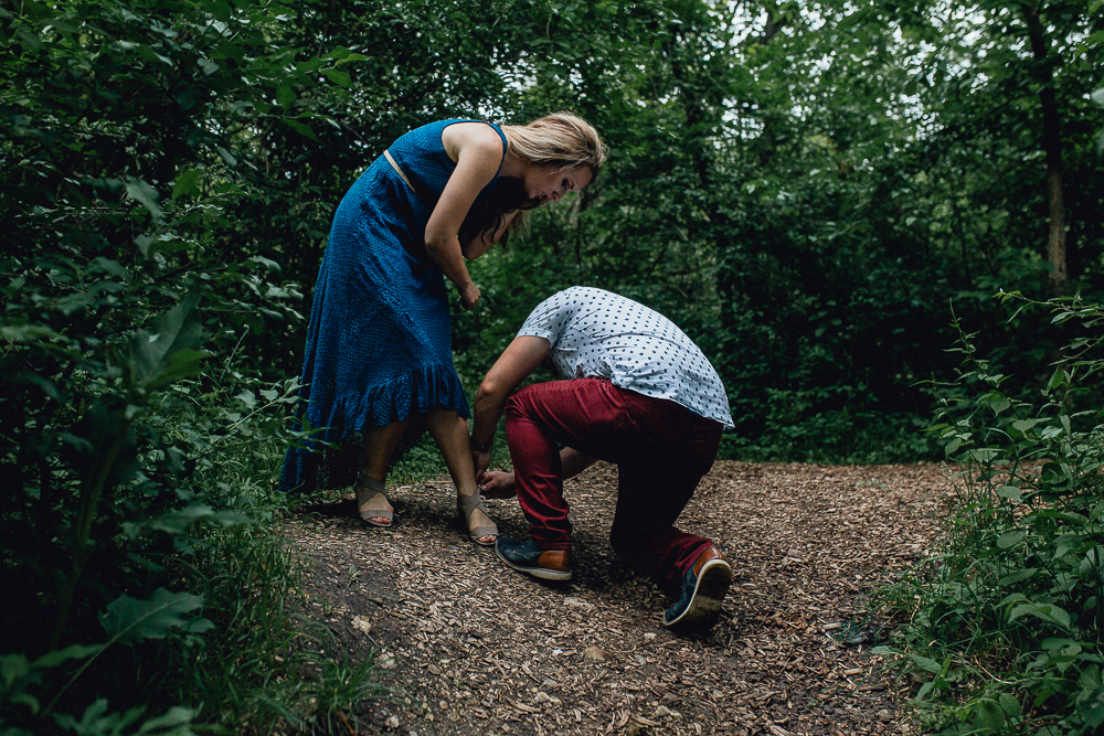 groom-helping-bride-with-shoes-by-waterfall.jpg
