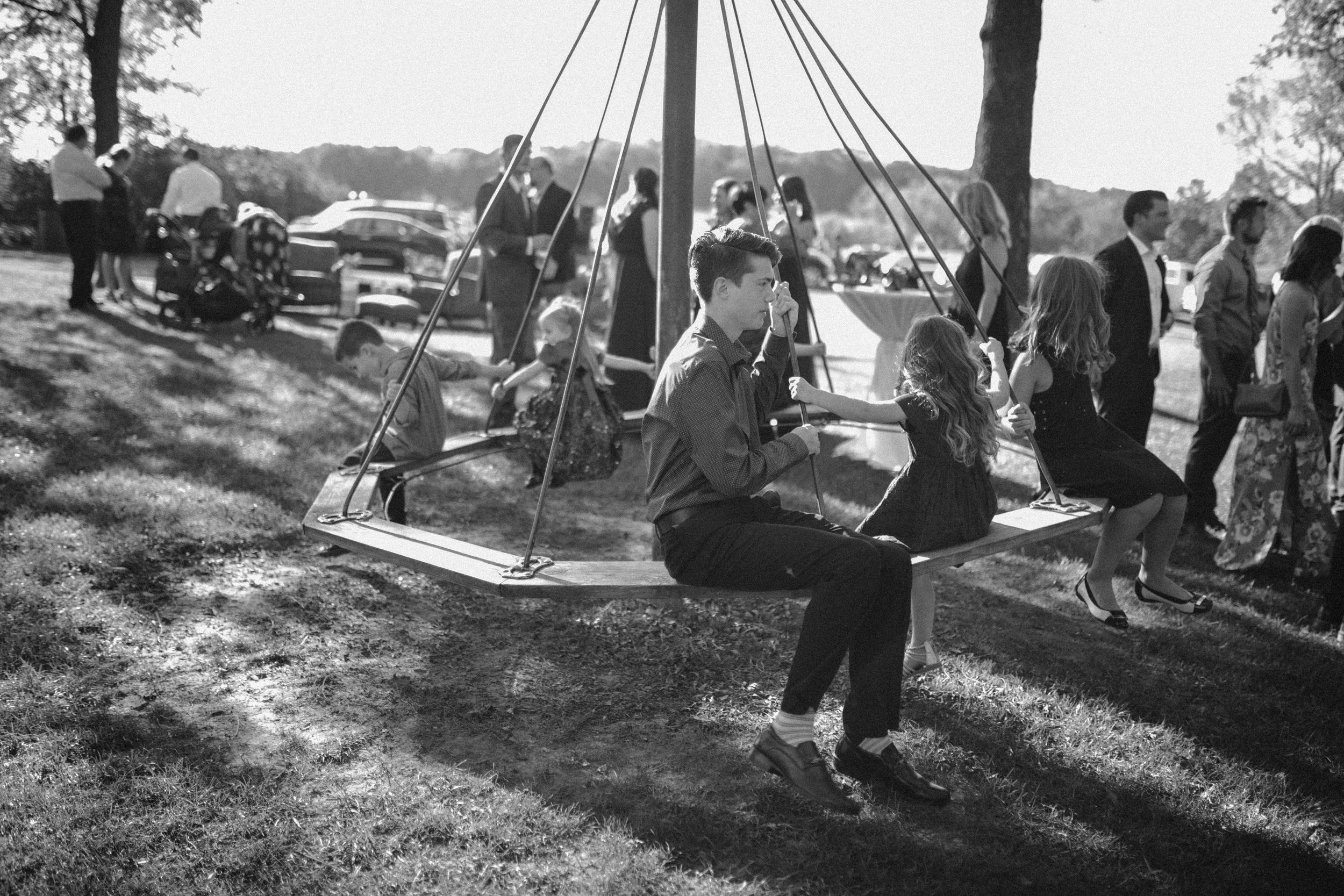 child on merry go round black and white at oak hill weddings