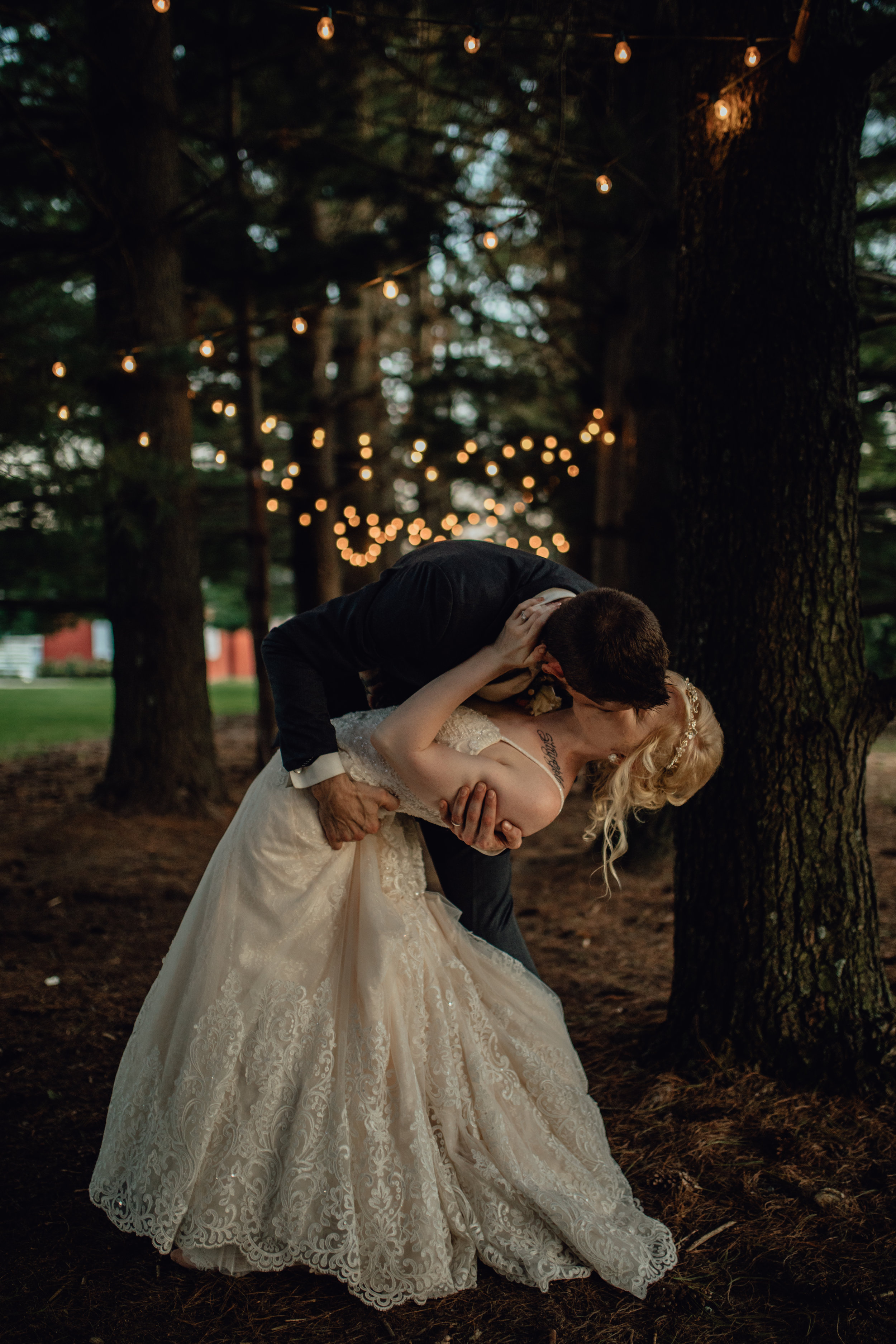 bride and groom dip under string lights in forest at oak hill weddings path of pines