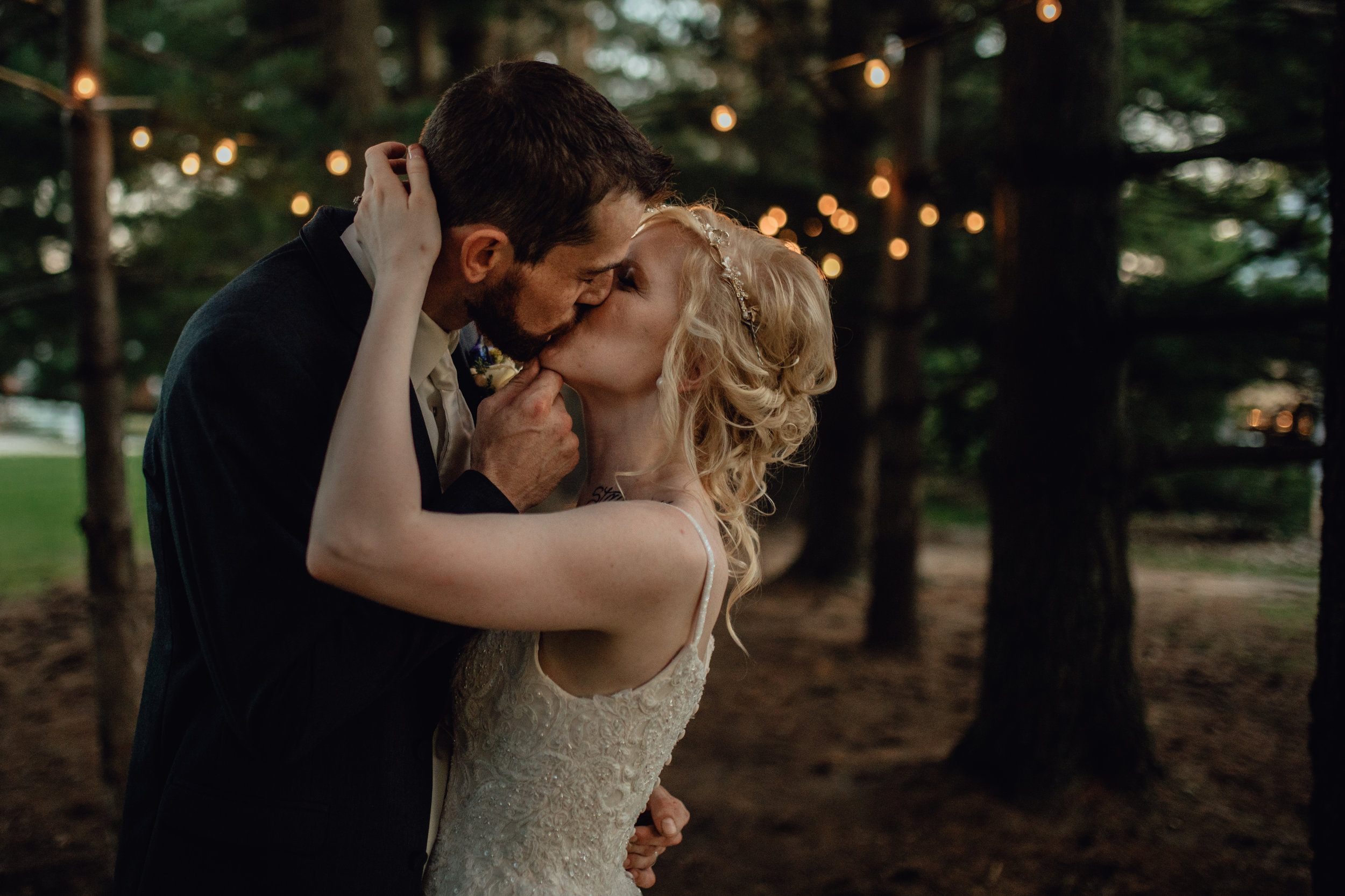 bride and groom kiss under string lights in forest at oak hill weddings path of pines
