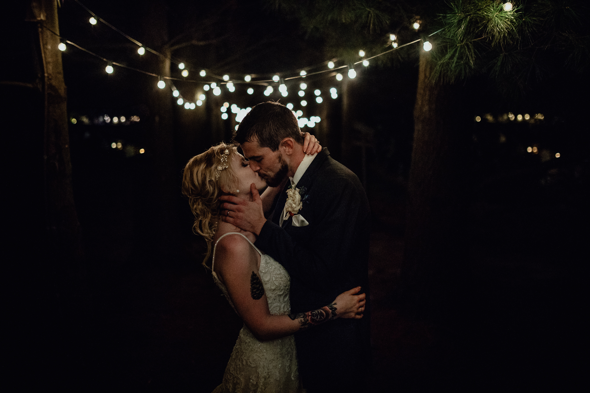 bride and groom kissing under string lights at oak hill weddings path of pines