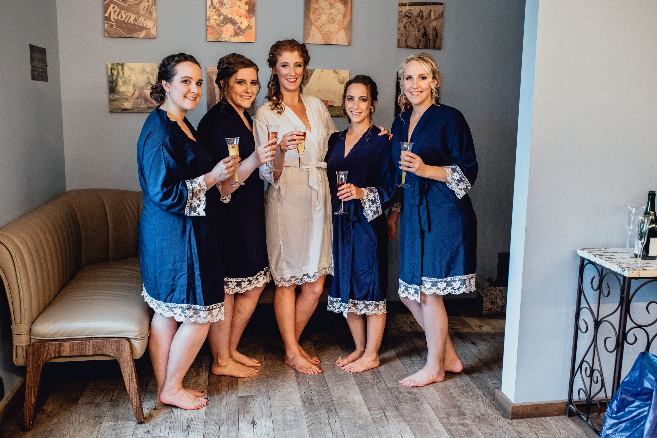 bride-and-bridesmaid-cheers-in-robes-in-bridal-suite-at-RUSTIC-MANOR-1848.jpg