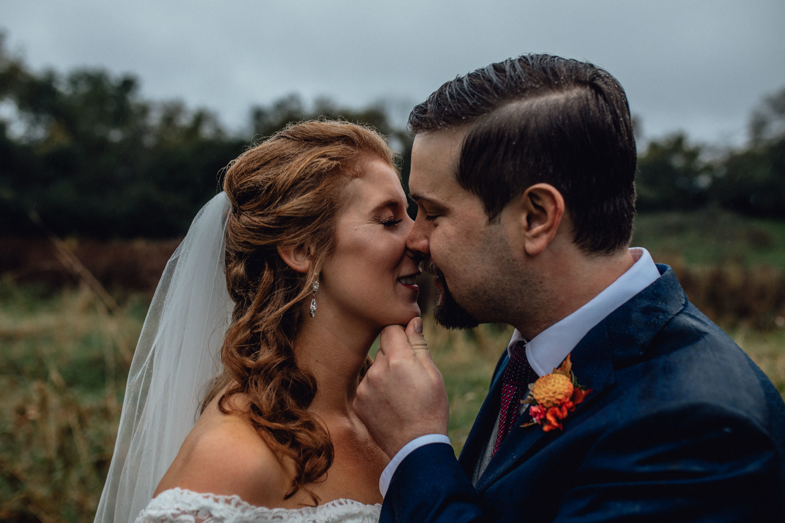 bride-and-groom-kiss-in-moody-field-portrait-at-rustic-manor-1848.jpg