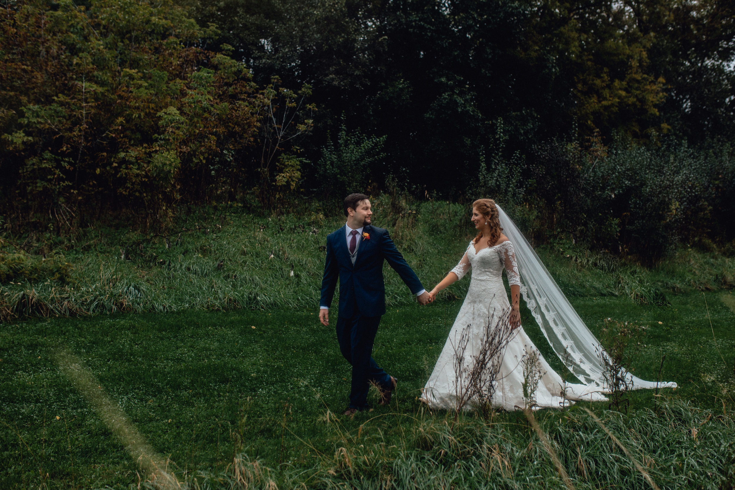 bride-and-groom-walking-in-moody-field-portrait-at-rustic-manor-1848.jpg