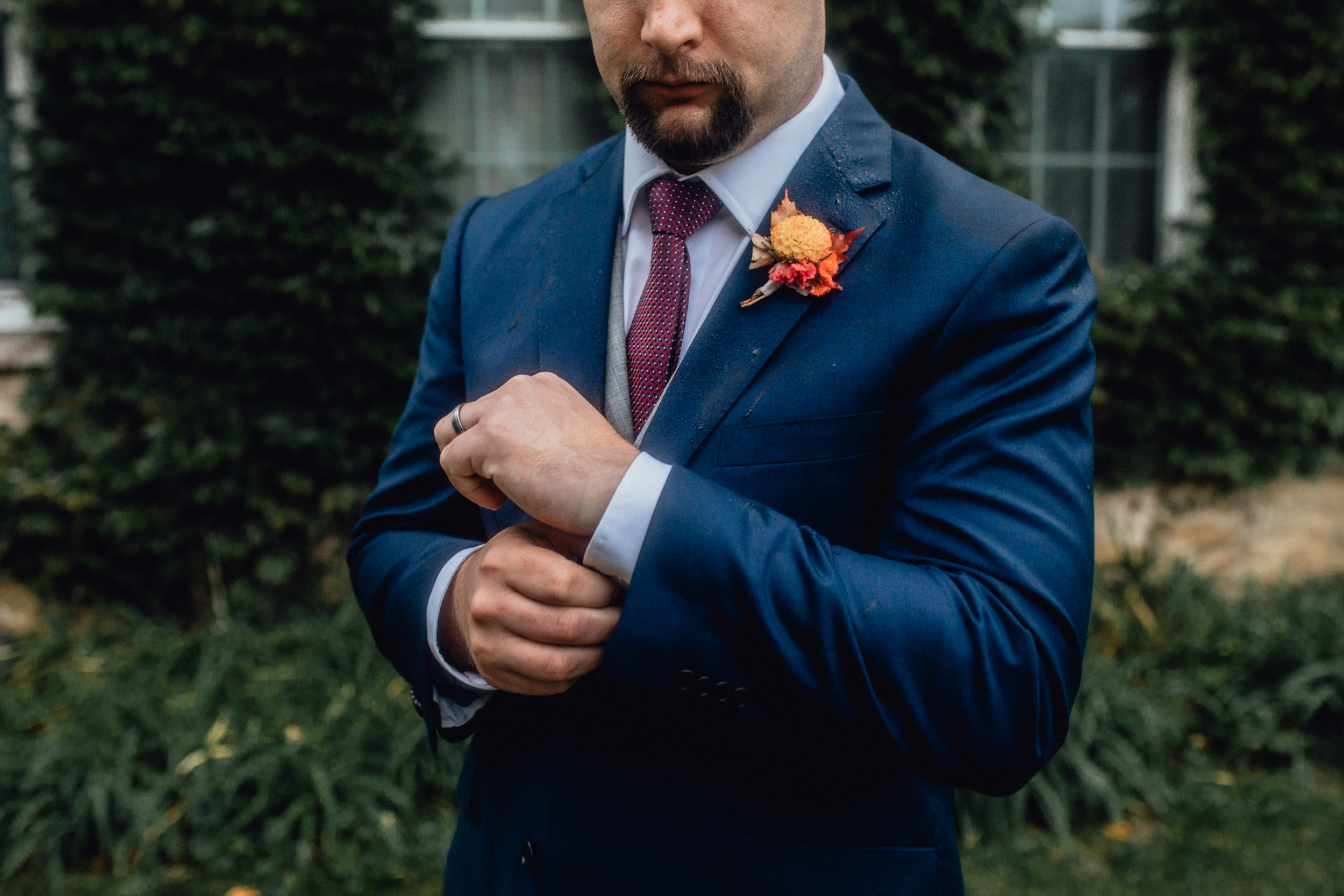 groom-buttoning-sleeve-at-rustic-manor-1848-with-ivy.jpg