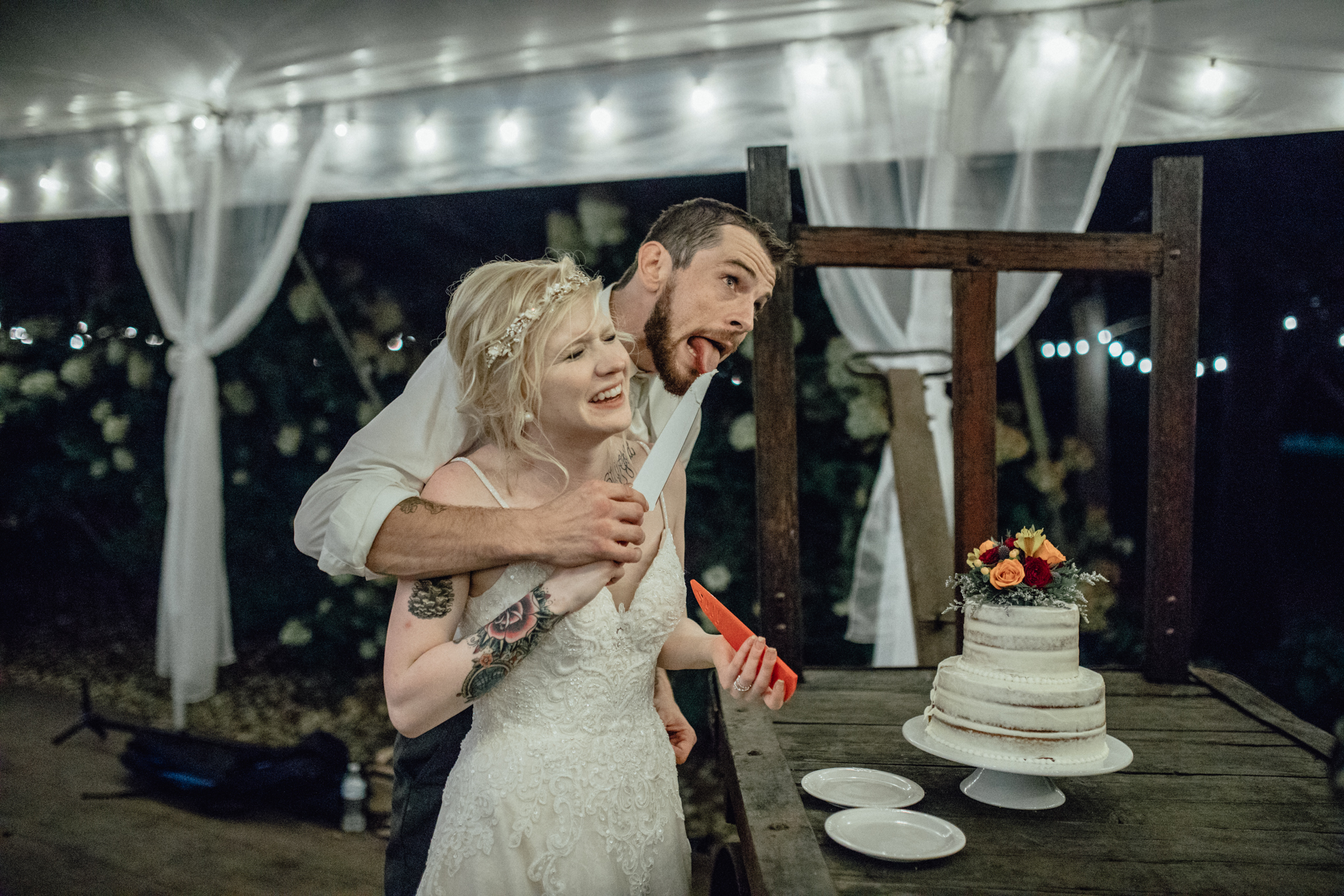 bride and groom cutting cake licking knife at oak hill weddings reception