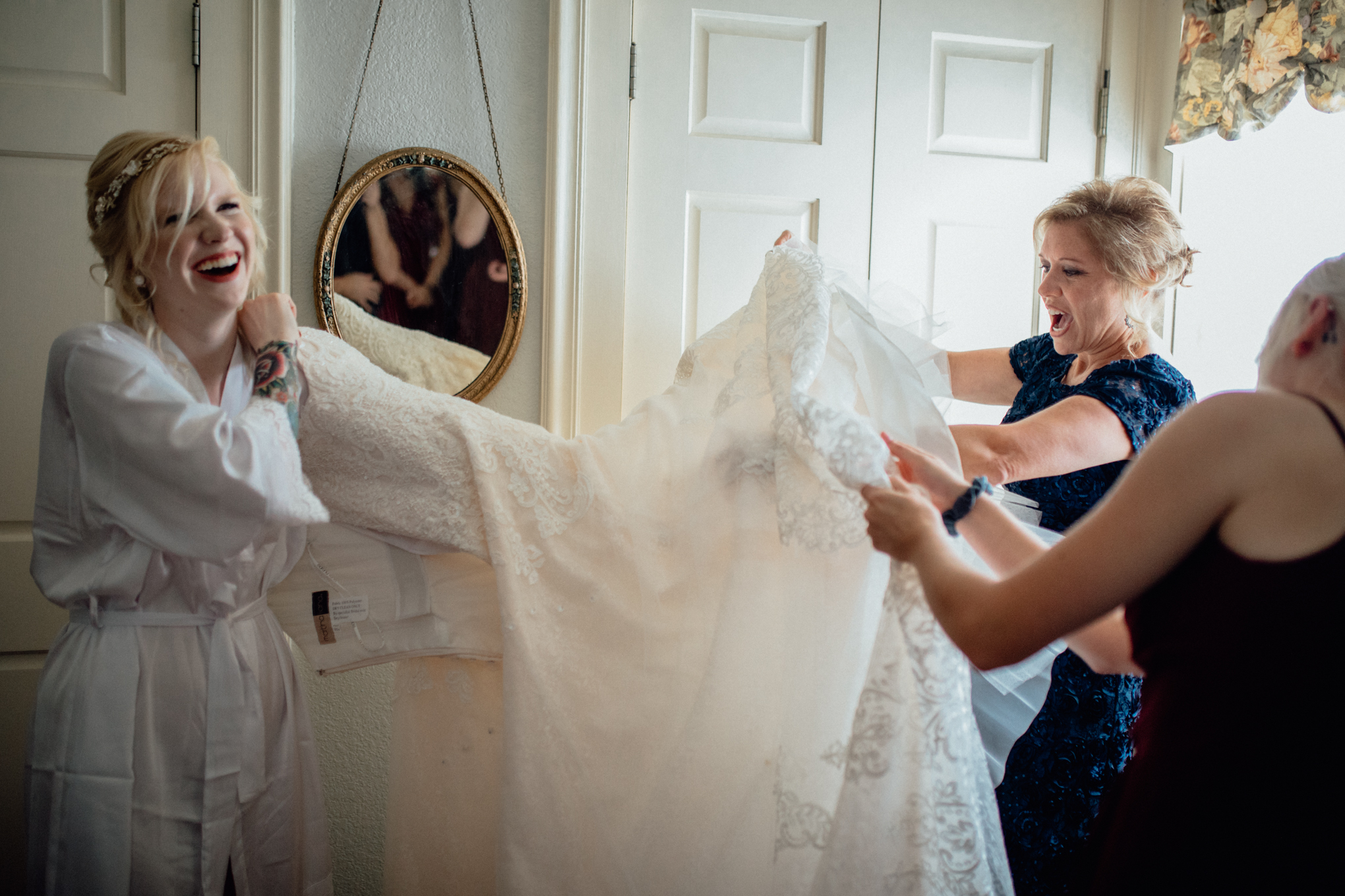 Mother and bridesmaid helping bride get dress off hanger
