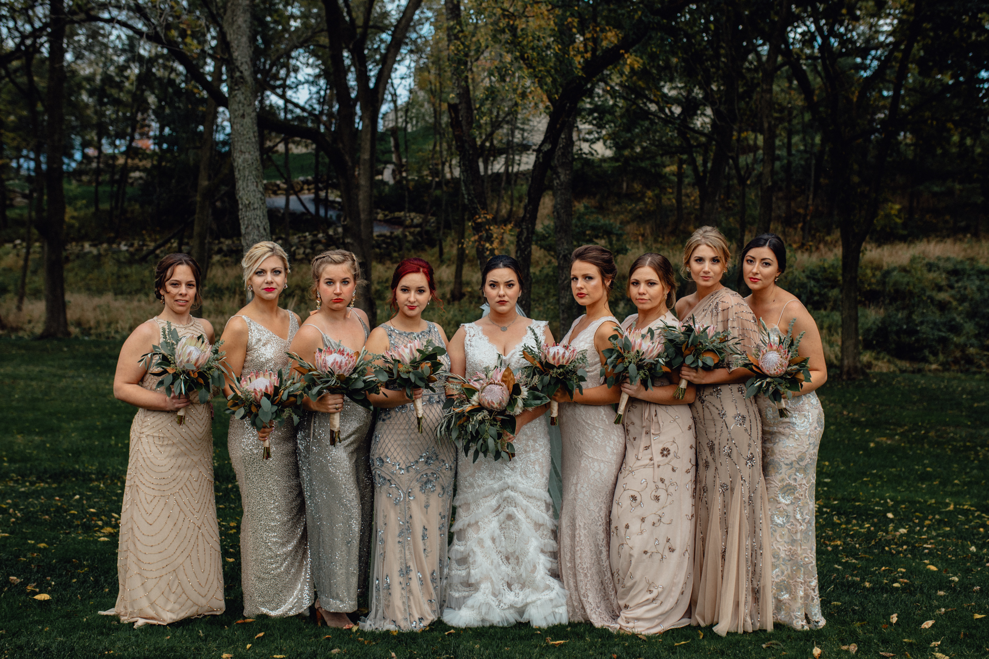 bridesmaids posing with bouquets in grass