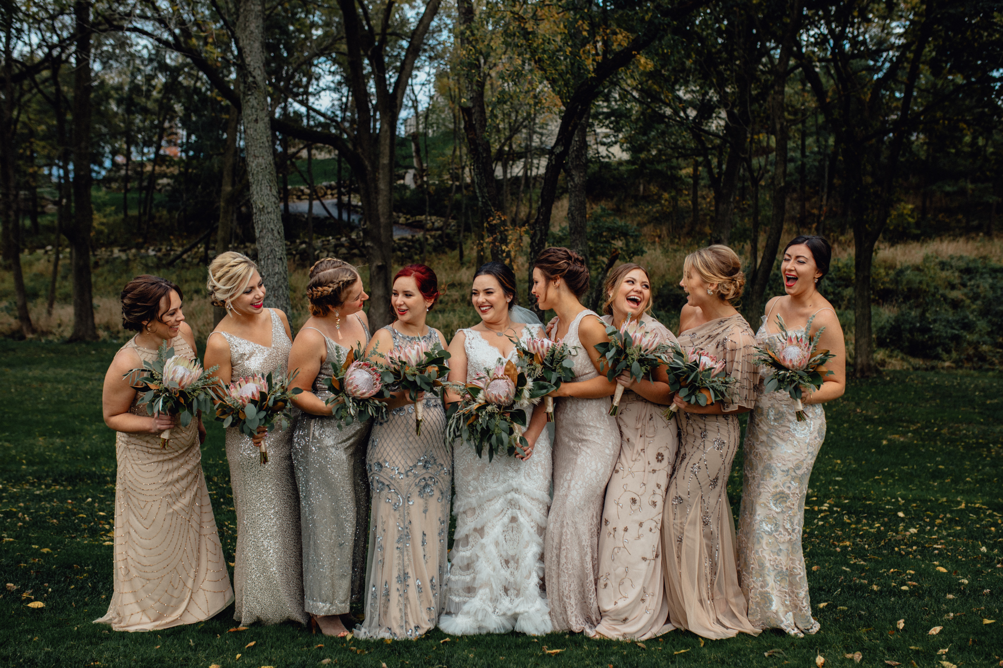 bridesmaids laughing with bouquets in grass