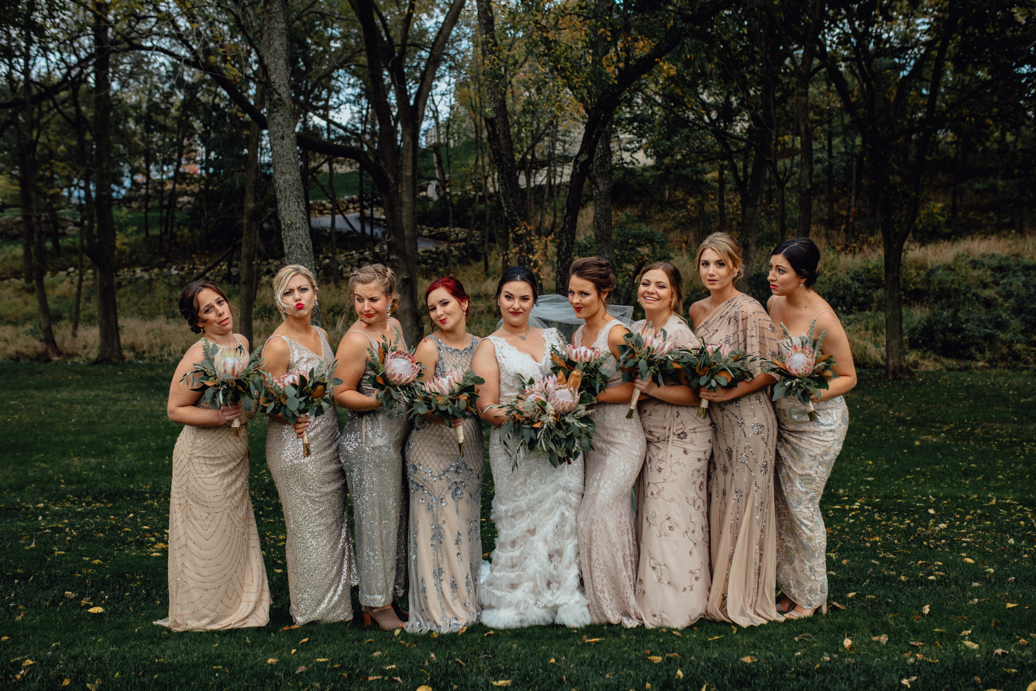 bridesmaids making kiss faces with bouquets in grass
