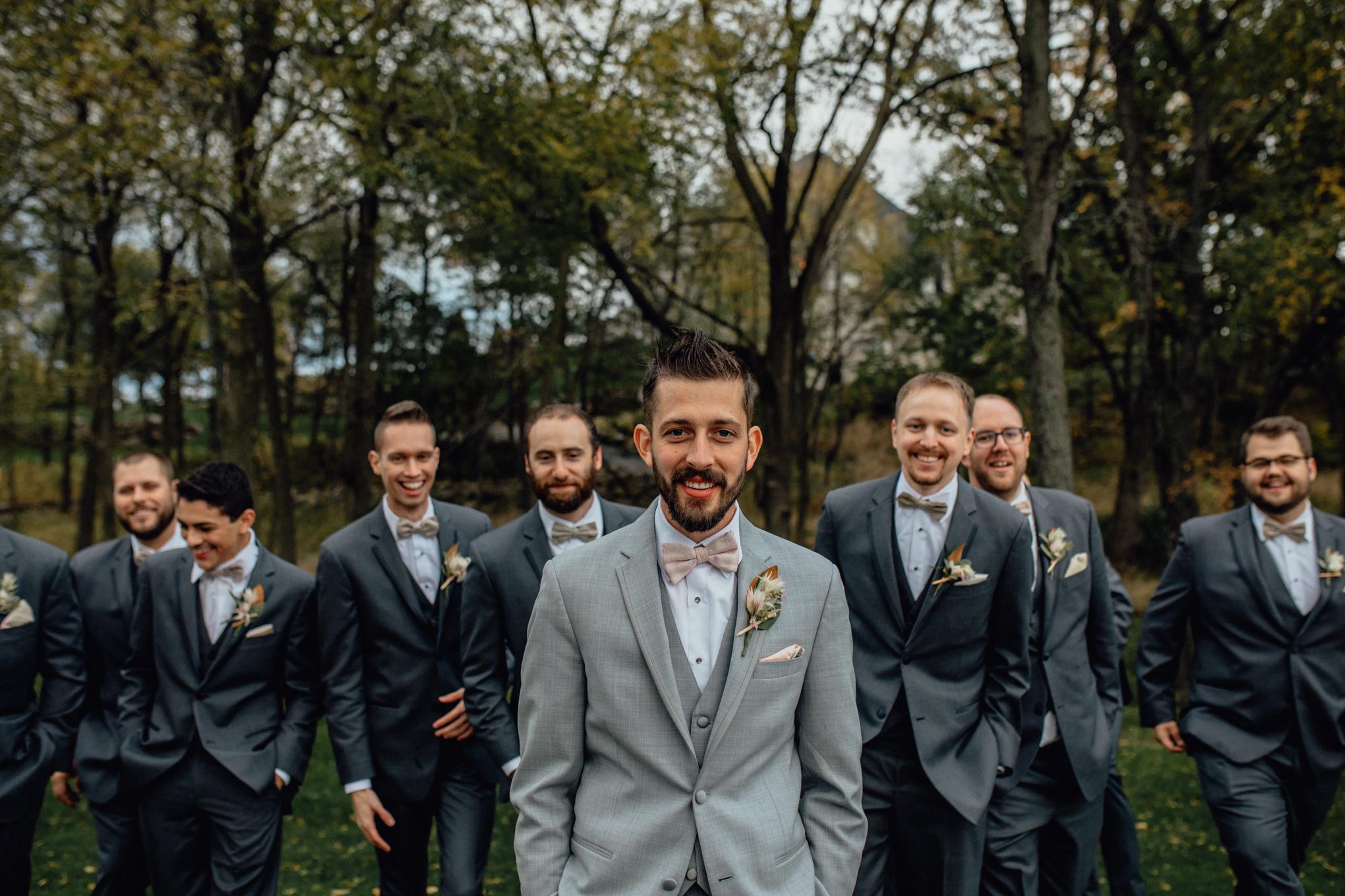 groom-walking-with-groomsmen-in-grass.jpg