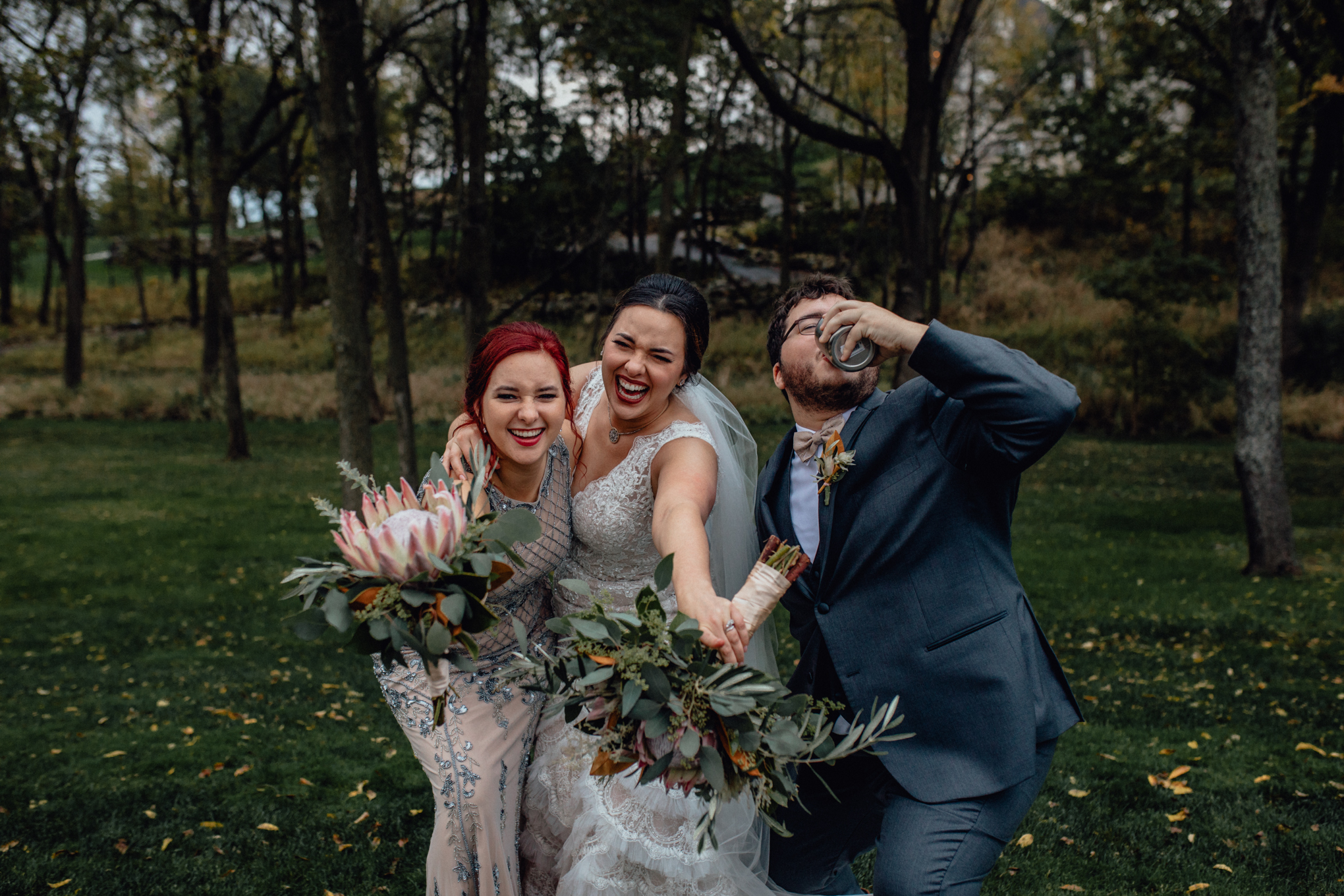 bridesmaid-and-groomsman-smiling-with-bride-in-grass.jpg