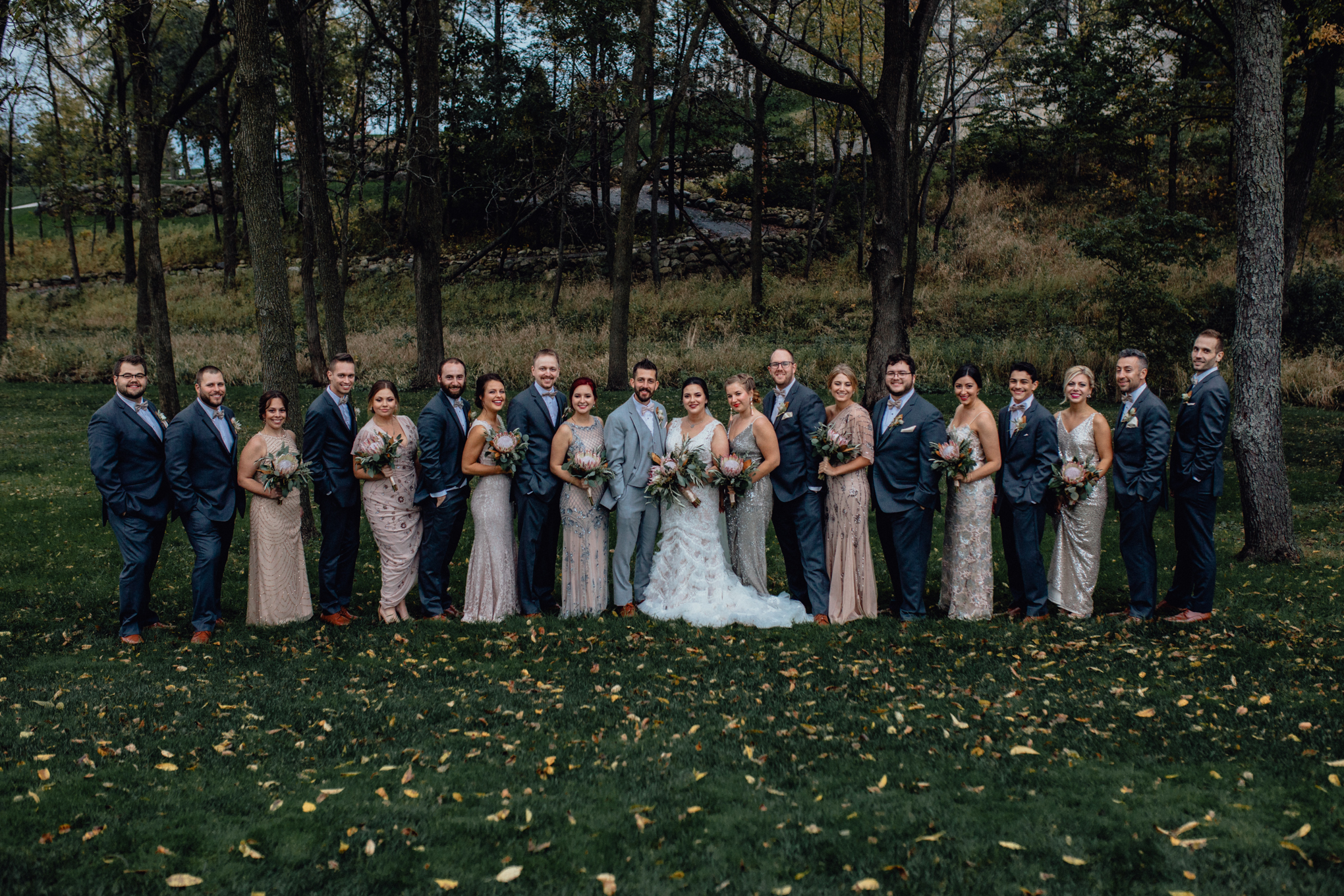 bridesmaids-and-groomsmen-smiling-in-grass.jpg
