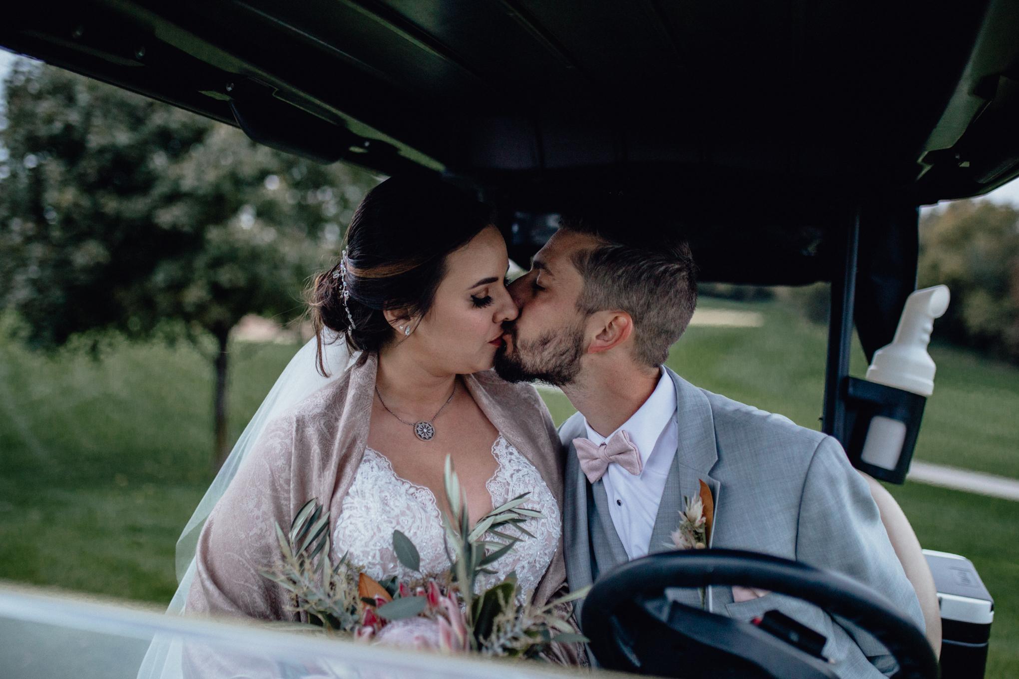bride-and-groom-kiss-on-golf-cart-at-brandybrook.jpg