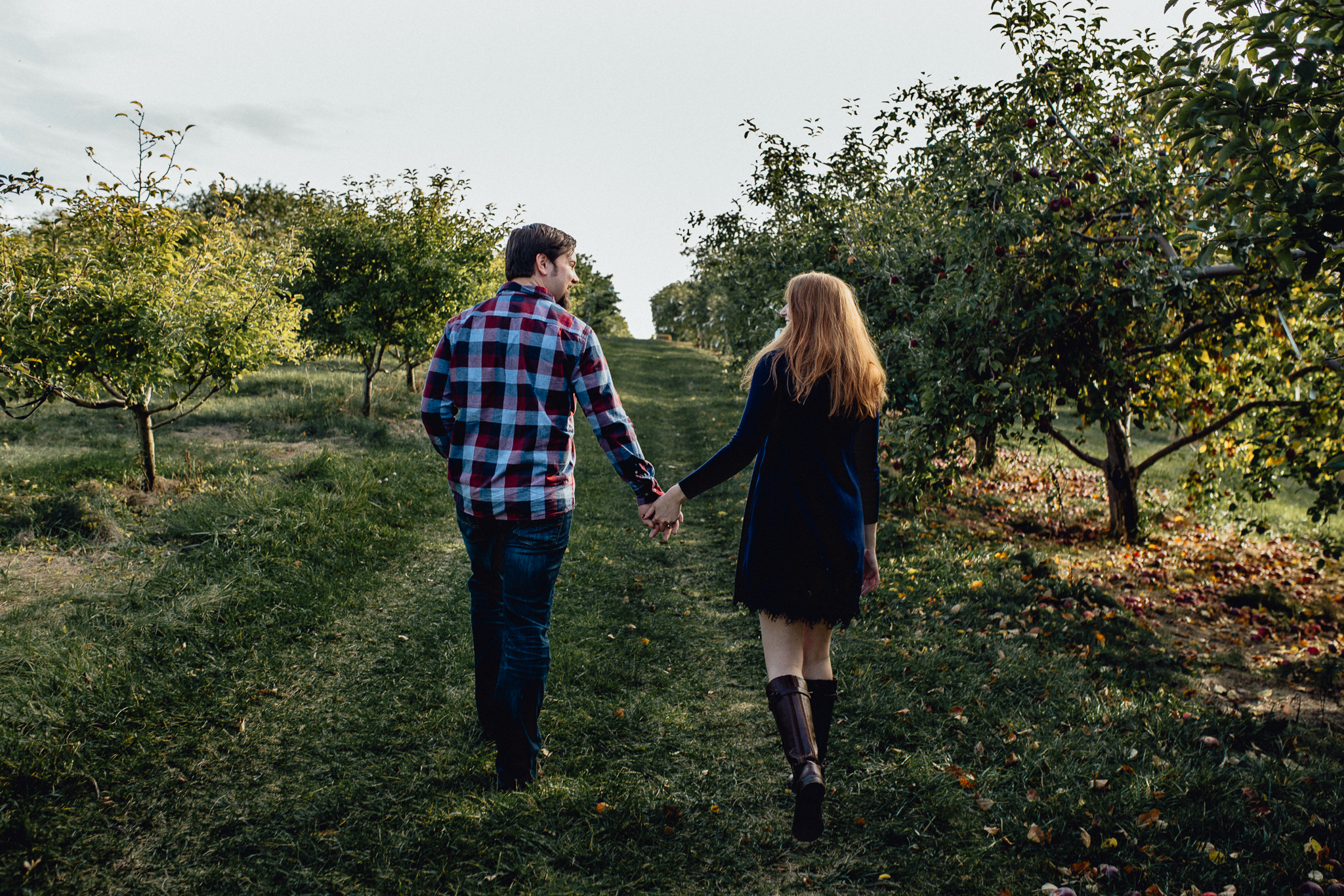 ENGAGEd-couple-walking-in-apple-orchard.jpg