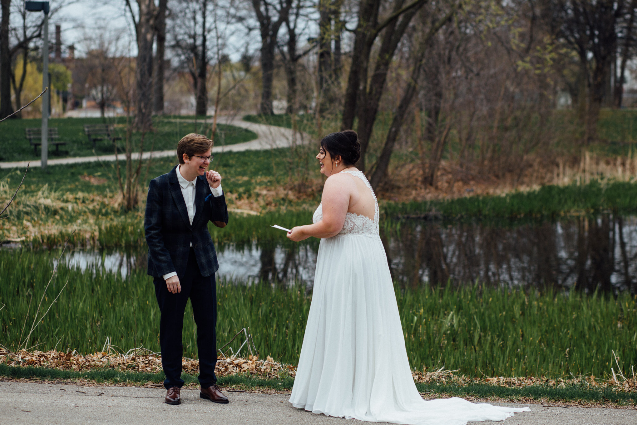 brides-laughing-exchanging-vows-during-first-look-at-humboldt-park.jpg