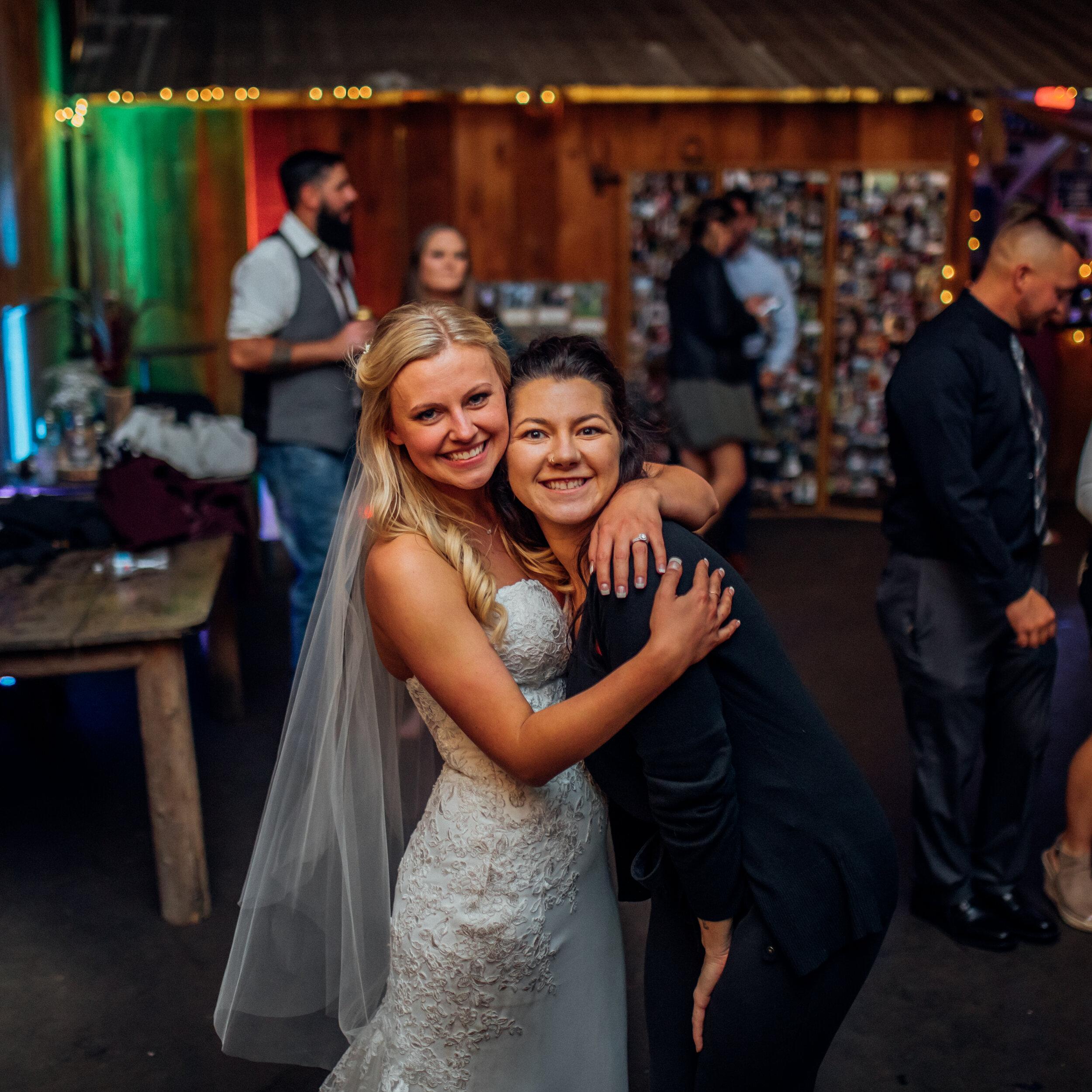kayla-of-emerald-tide-photography-hugging-bride-at-kettle-moraine-ranch-wedding.jpg