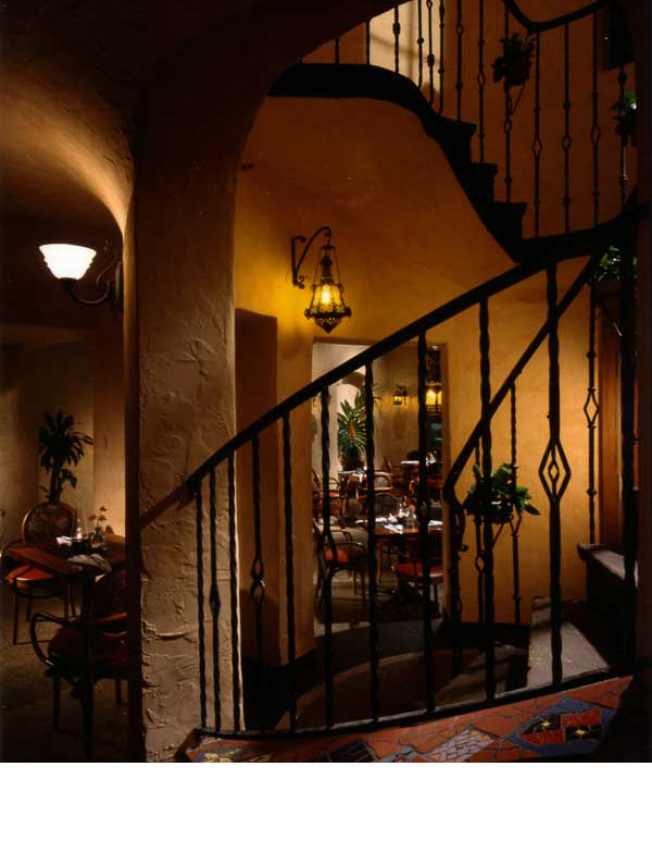 Existing iron staircase railings were complemented with antique Mexican sconce lights and mosaic tile.