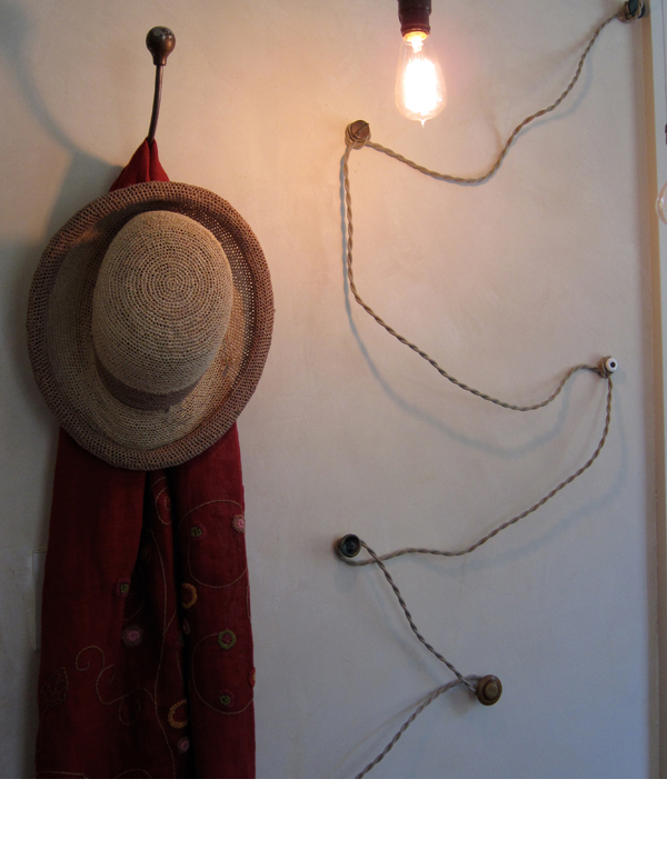Vintage buttons attached to the wall, catch the cords leading to the ceiling.