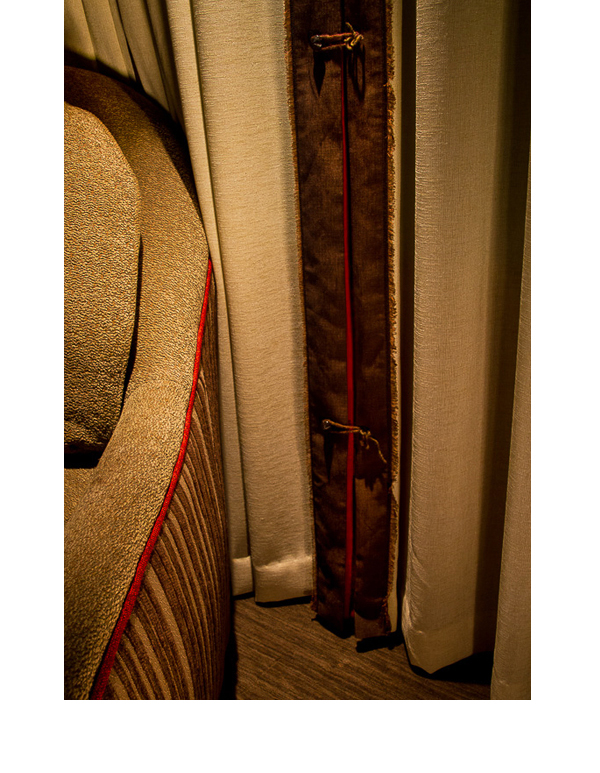 Red inserts in curtains complement red walls and cabinets in the room.